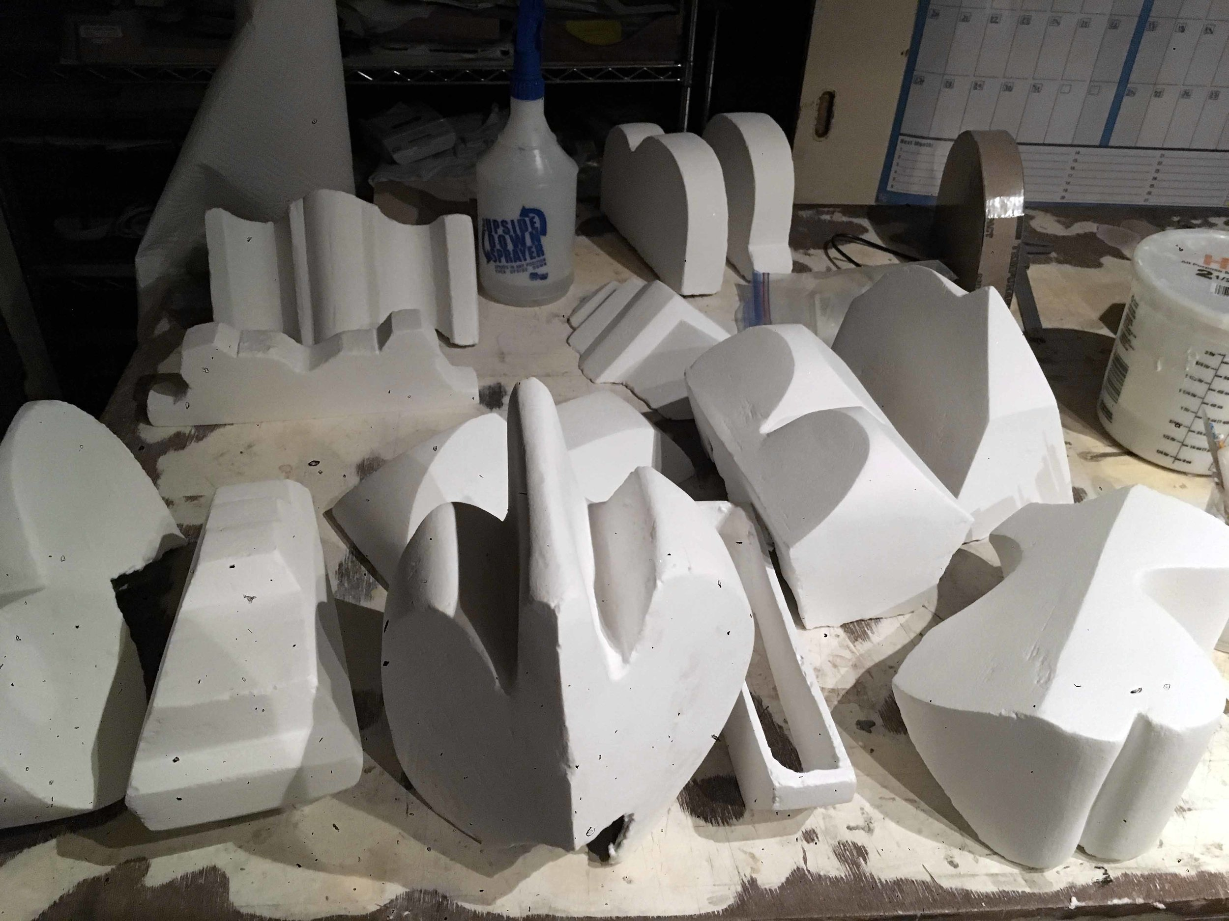 The white appearing forms is the clear paste applied to cardboard forms, before they are coated with a layer of color and fired