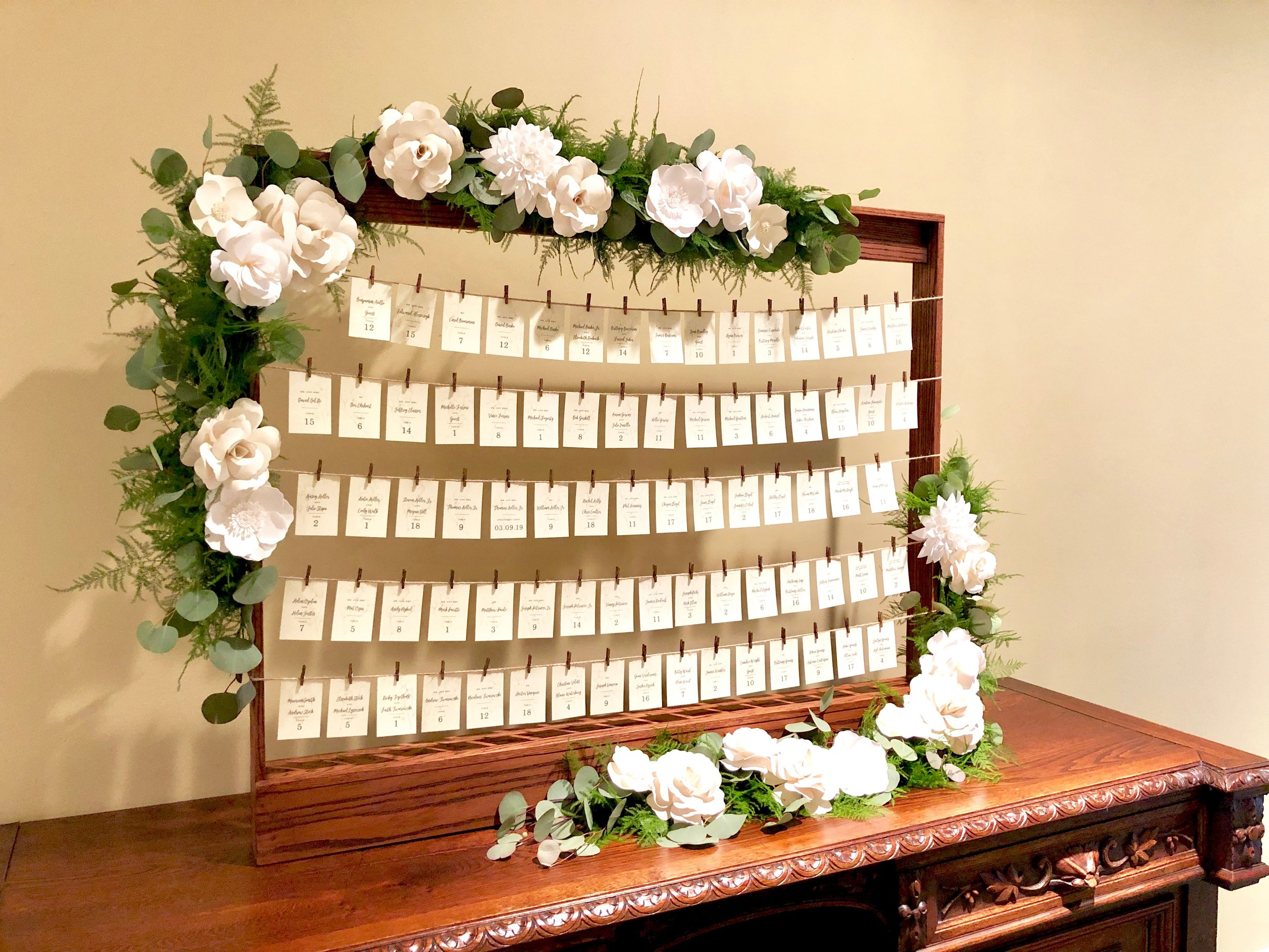"Clothespin Place Card Holder - Rental Rate: 75.00 Undecorated, 115.00 Decorated with live greenery garland and paper flowers in color(s) of your choice. Custom place cards can be purchased separately for 0.50 each.Dimensions: 42""L x 34""H x 4""WQuantity Available: 1Includes mini clothespins in your choice of natural or espresso stained wood."