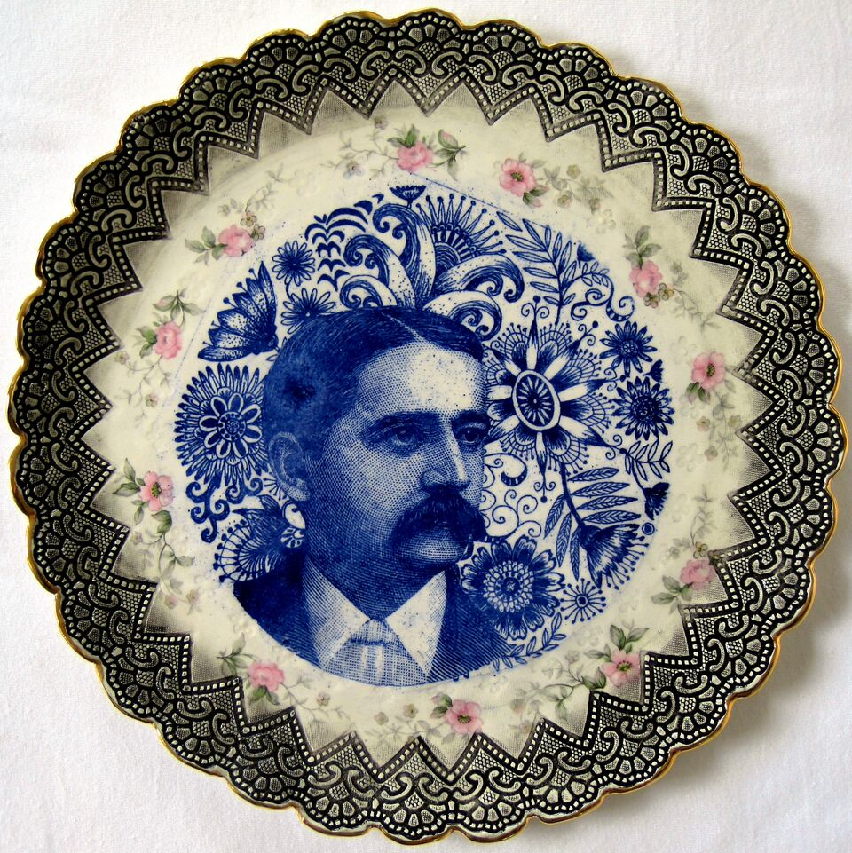 Painted ceramic plate with a mans face and filigree border