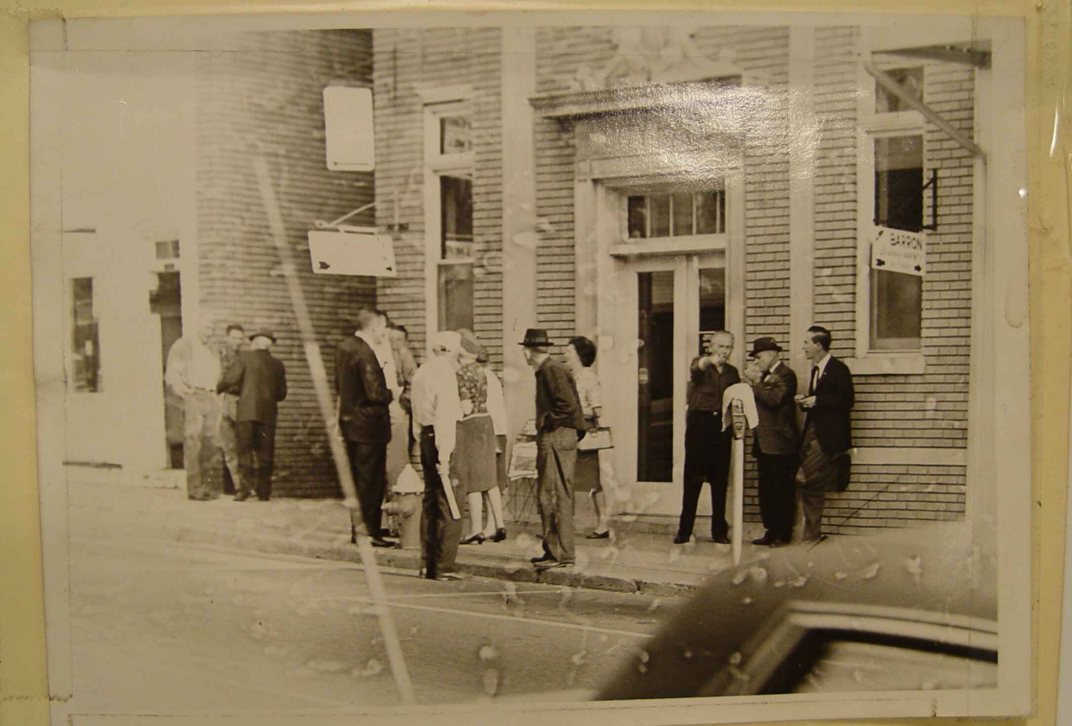People gathered outside City Hall and Barrons Insurance Agency. Notice the parking meters on Main Street.