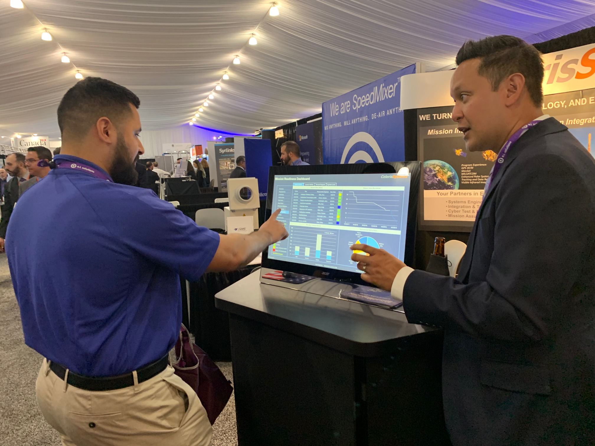 Celeris Systems Vice President Rob Enrico shares iRIS® touchscreen dashboard capability with a symposium attendee.