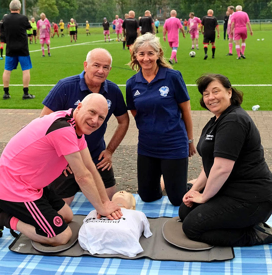 Liz Crawford Projects Officer with St John Scotland teaching Minister Joe FitzPatrick and WFS Trustees Gary McLaughlin and Vivian Wallace some CPR.