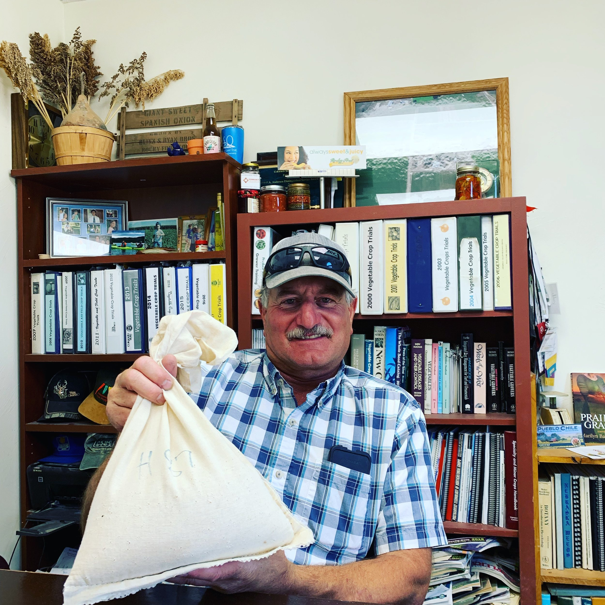 Dr. Mike Bartolo Holding the Bag of Seeds that Birthed the Pueblo Green Chile.