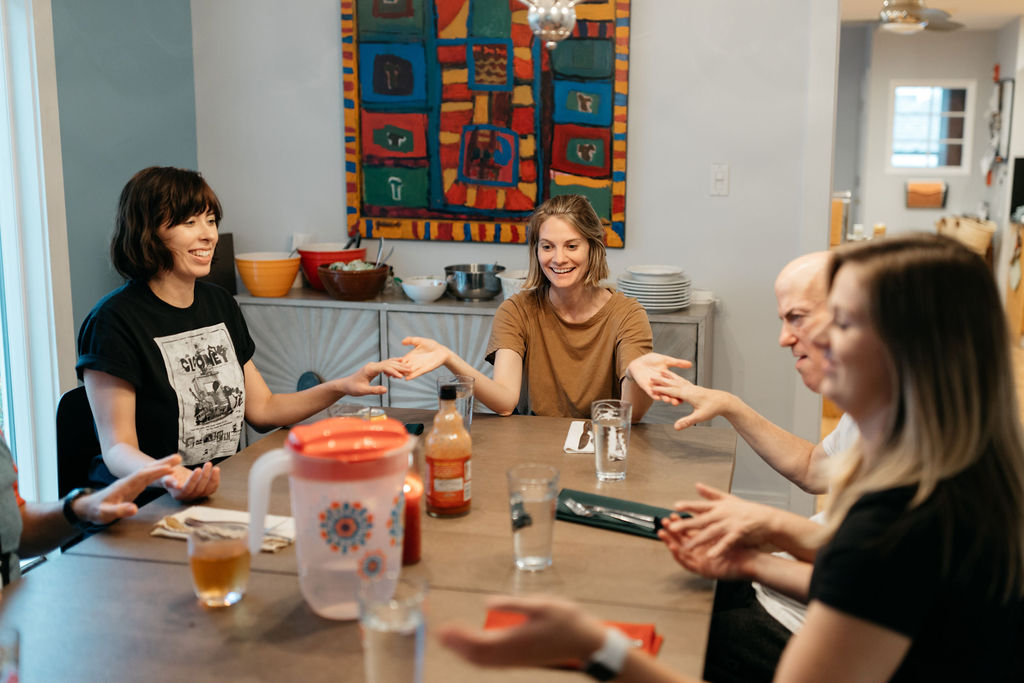 Lena, Kendall, John and others sharing dinner at Peace House.