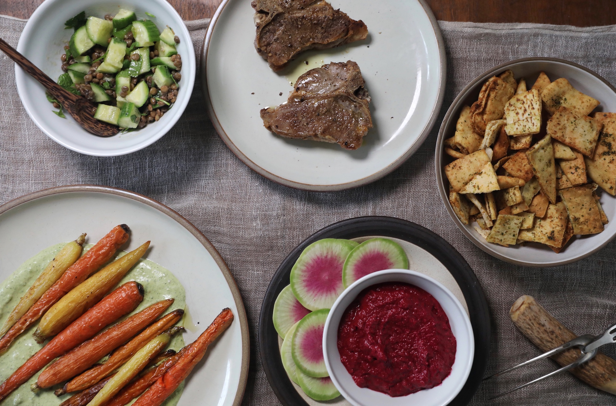 A peek at the little Middle Eastern inspired dinner spread I made, including a take on Israeli salad, roasted carrots on a labneh zhoug sauce, roasted lamb, and roasted beet and garlic dip.