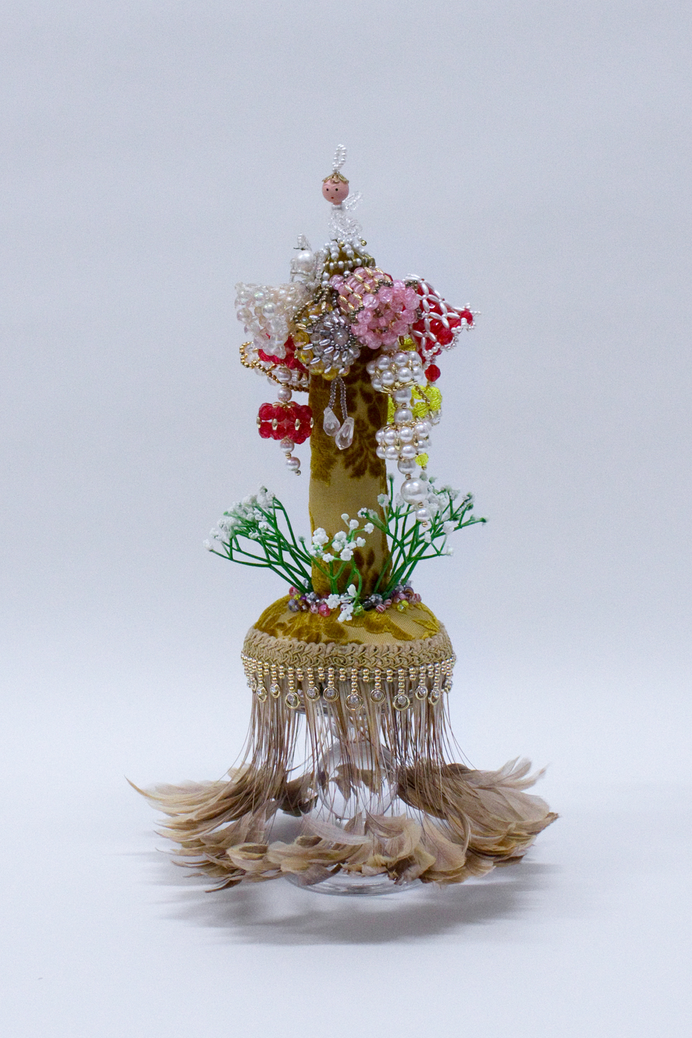 """Flight,  Crystal and plastic beads, found fabric, trim, ornaments, plastic flowers, polyester batting, thread, glass stand, 8 x 8 x 14"""", 2019"""