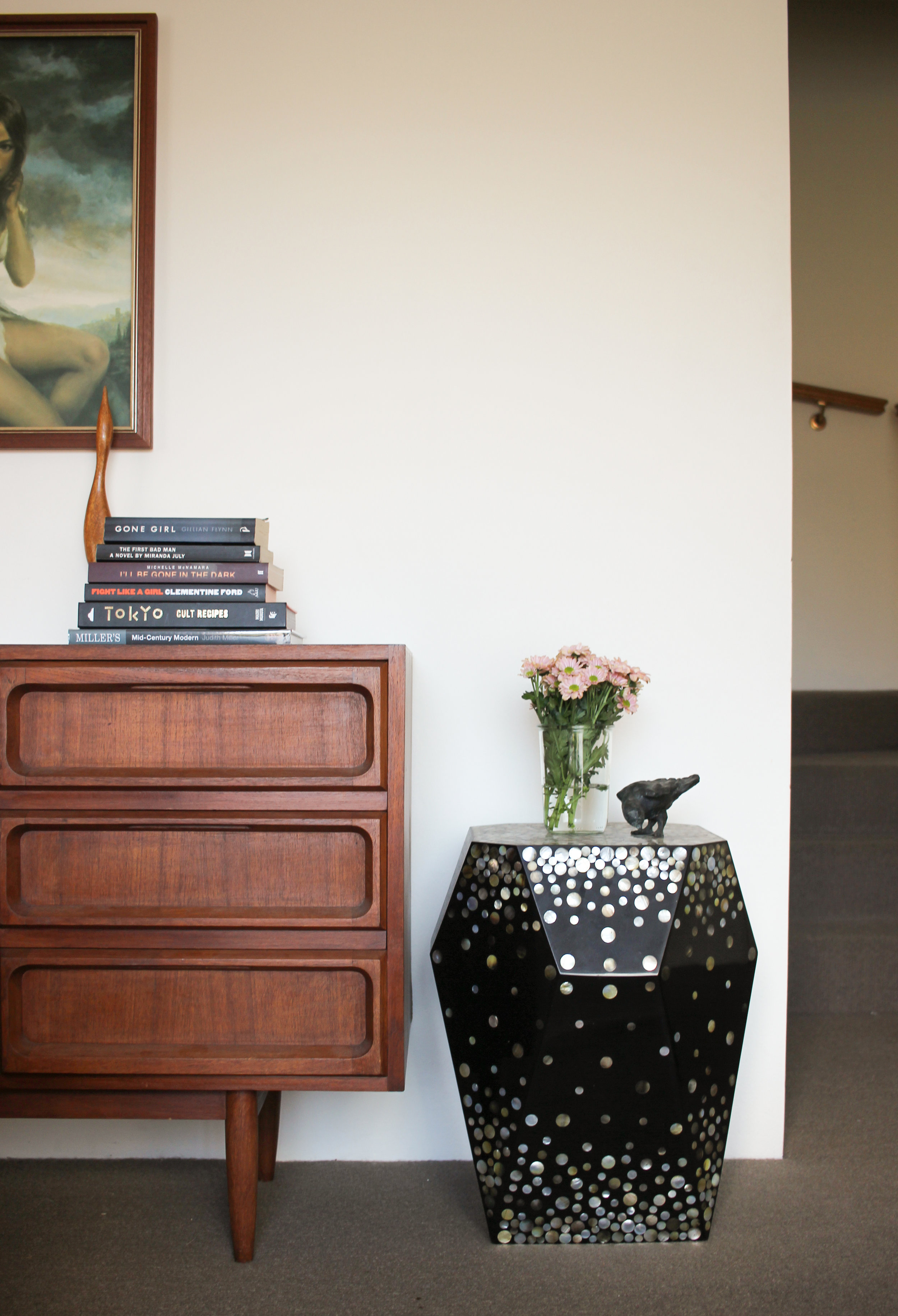 """This black side table is a big feature in my space, so I like to style it with black books nearby to share the heavy """"black"""" load in the space."""