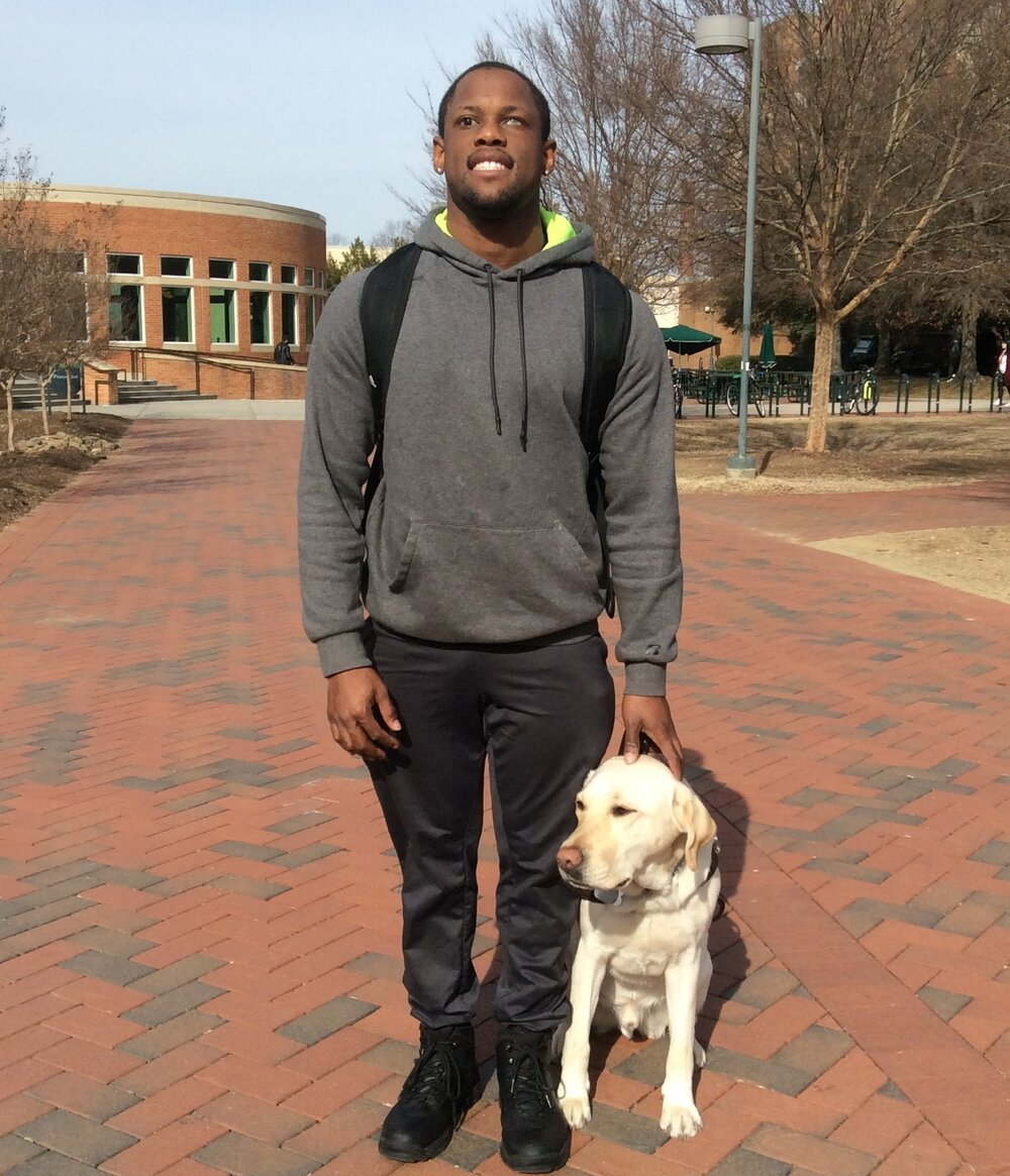 student in a grey hoodie with a dog