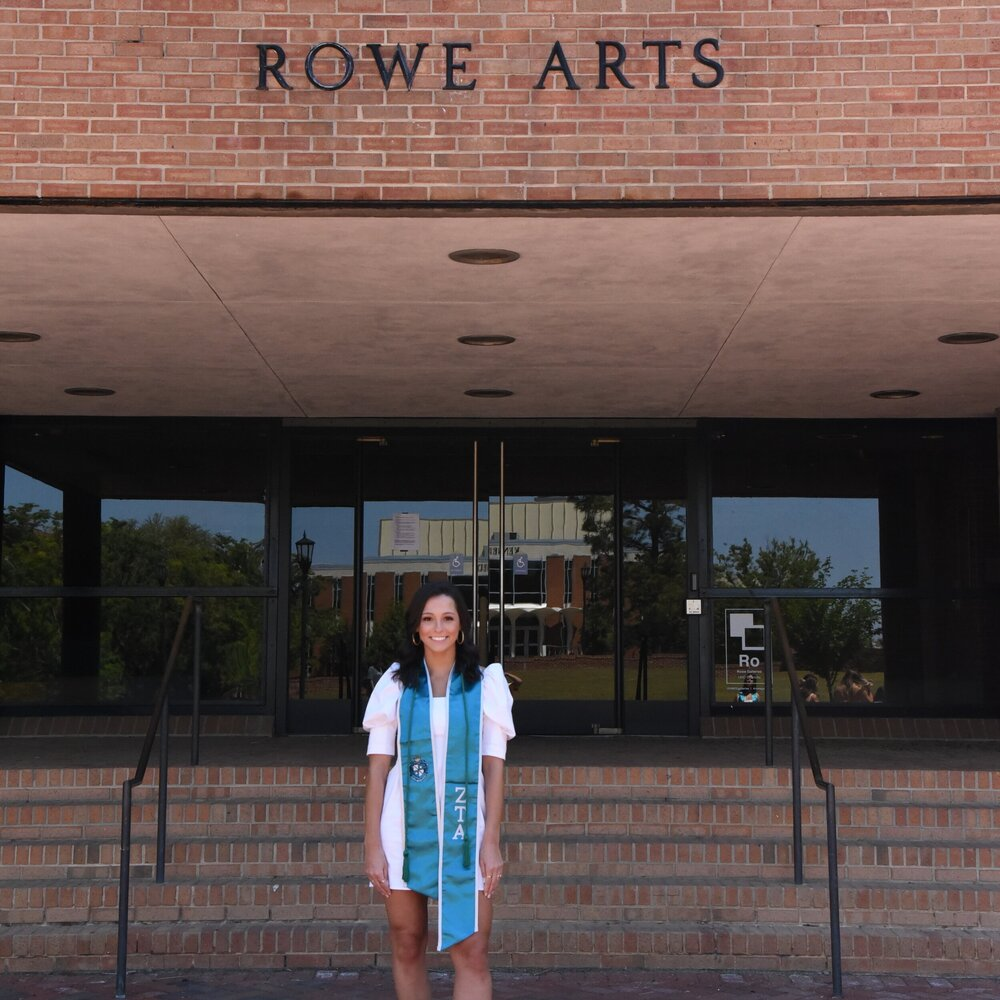 student standing in front of rowe arts