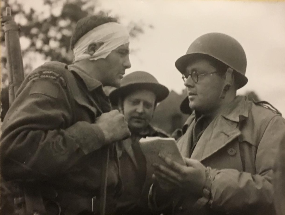 Official Canadian War Photograph of wounded Rfn. Al Jesson with a Canadian war correspondent taking notes following the battle at Carpiquet (1944).