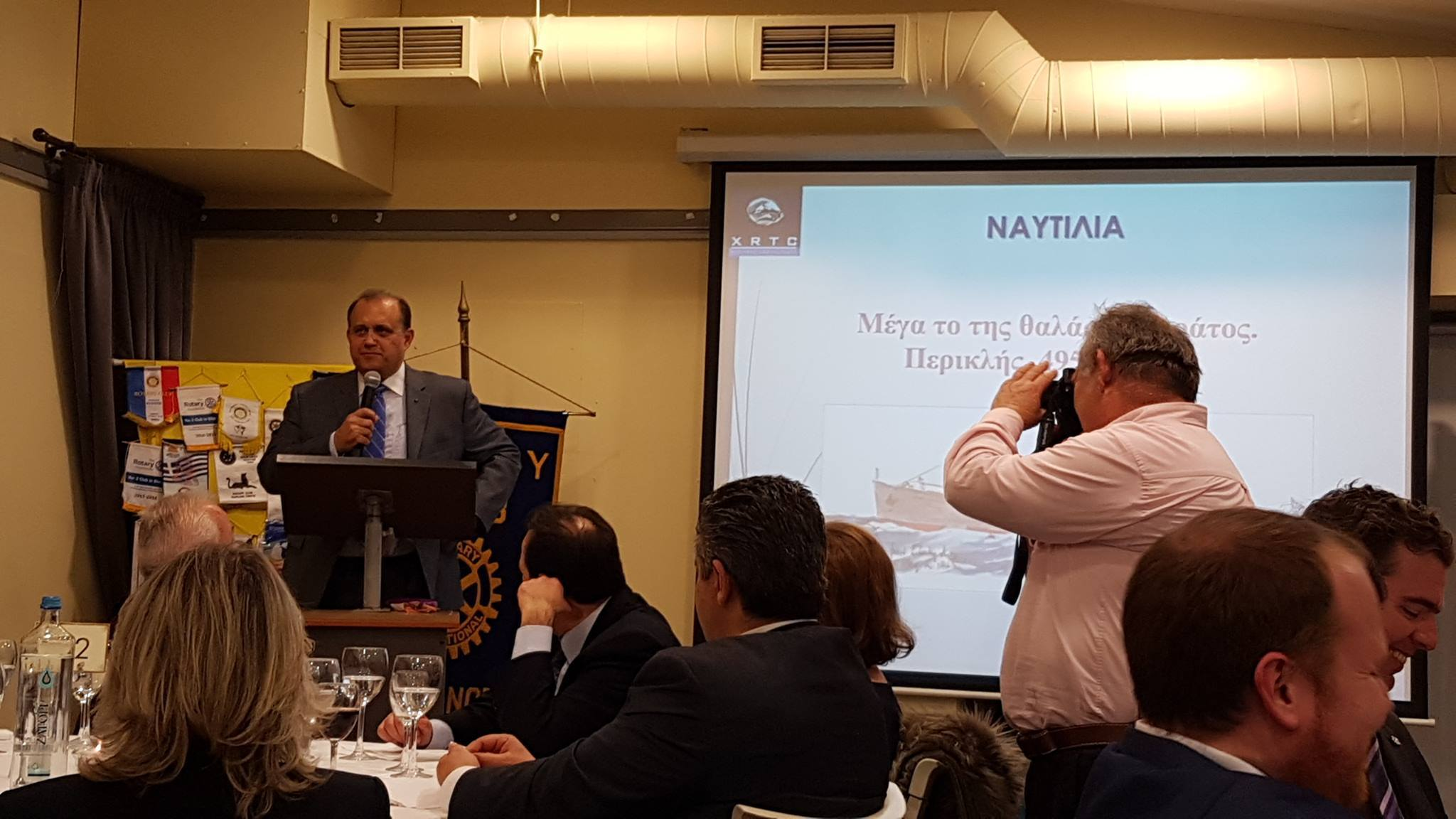 Nick Larigakis providing a greeting at a dinner hosted by the Rotary Club of Maroussi.