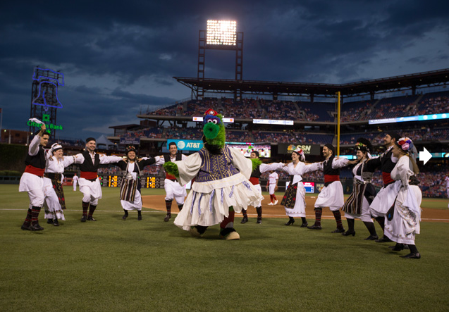 The Pan-Macedonian Dance Group dancing around The Phillie Phanatic on the field during the 5th Inning