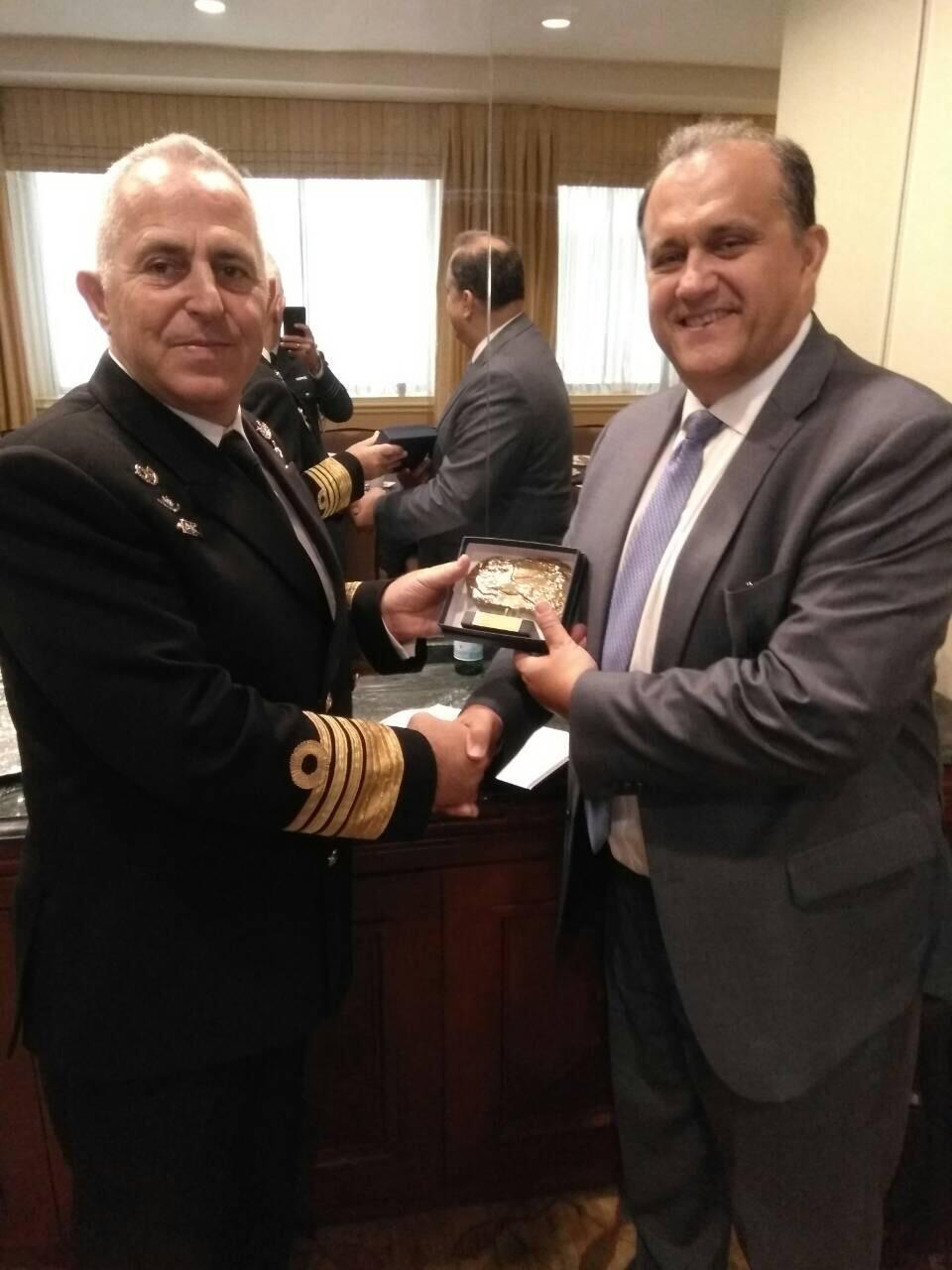 Admiral Apostolakis presents a memento to AHI President Nick Larigakis.
