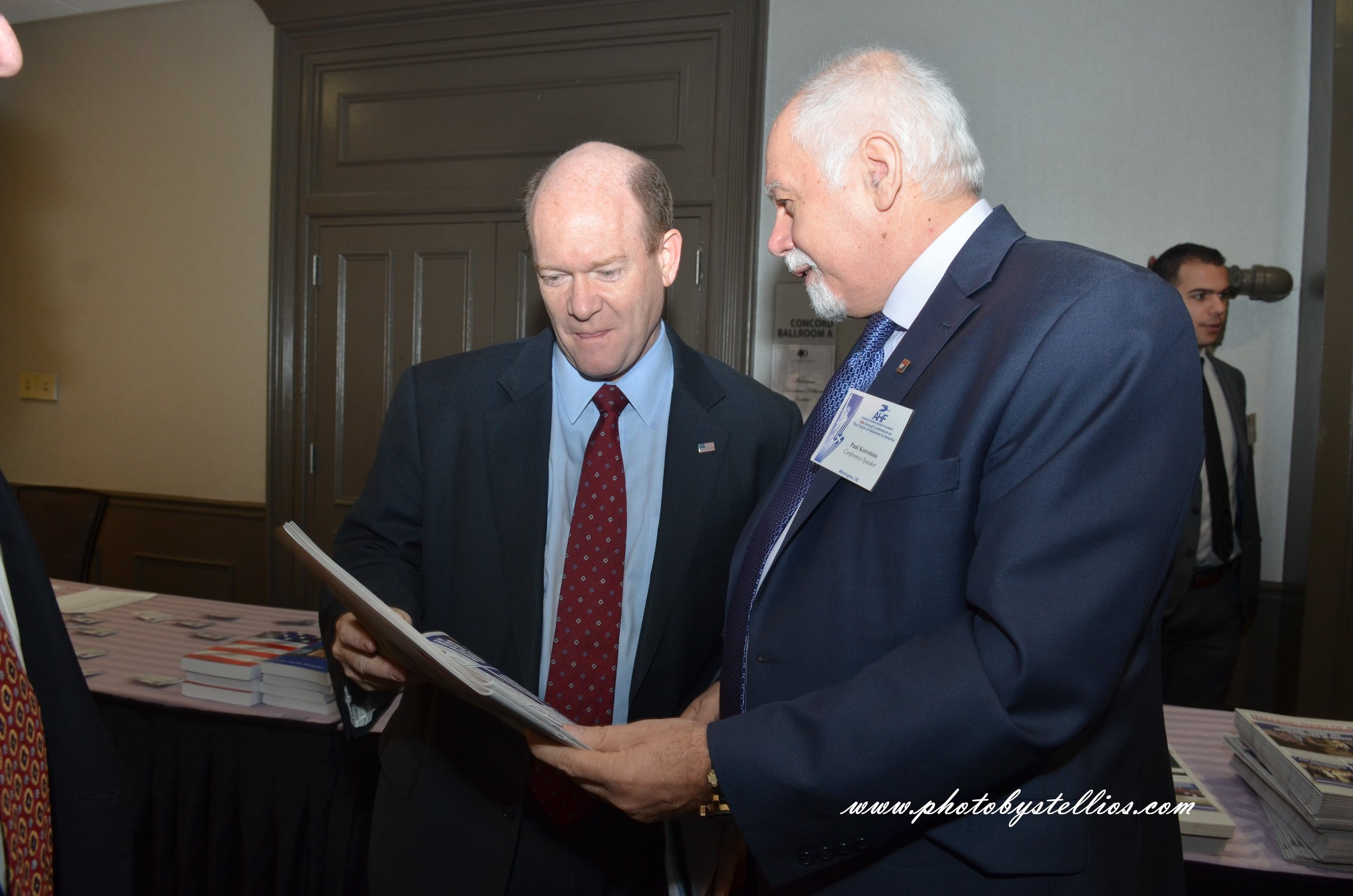 Paul Kotrotsios presents a copy of The Hellenic News of America to Senator Chris Coons.