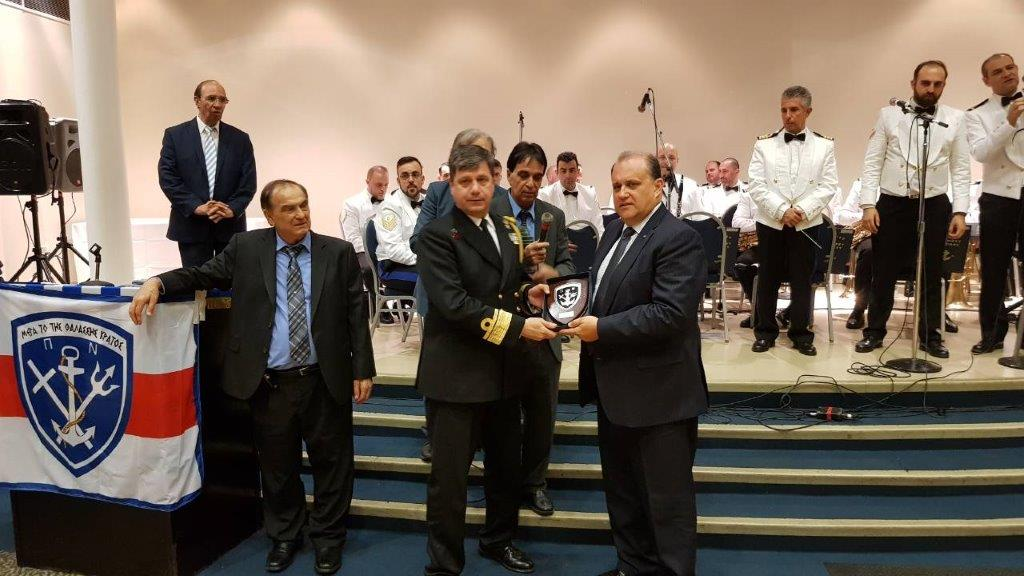 Rear Admiral Ioannis Paxivanakis presents Nick Larigakis with an honorary plaque.