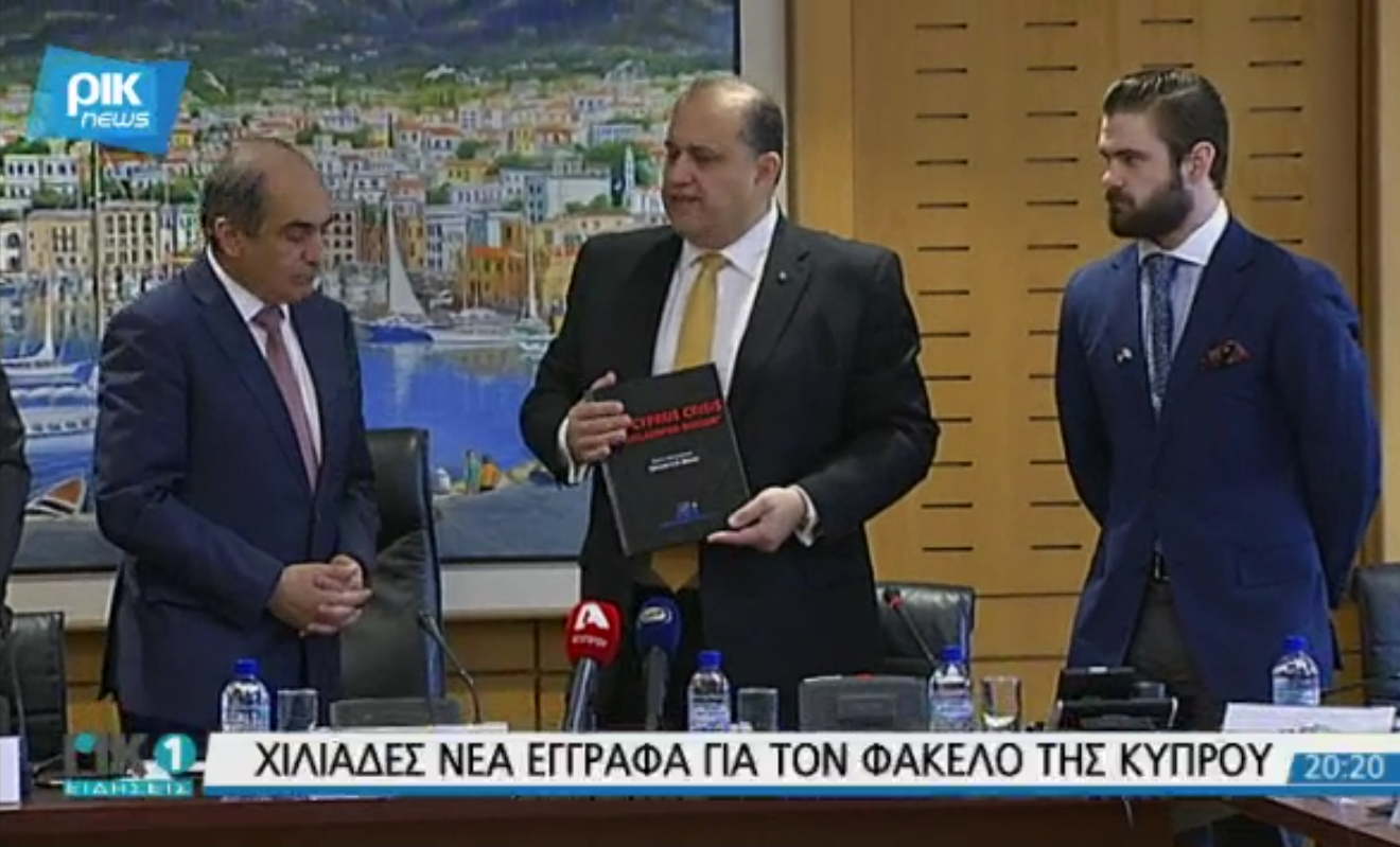 """President of the Cypriot House of Representatives, Demetris Syllouris, AHI President Nick Larigakis holding a copy of """"The Cyprus Crisis,"""" and AHI Graduate Fellow Gregory Graves."""