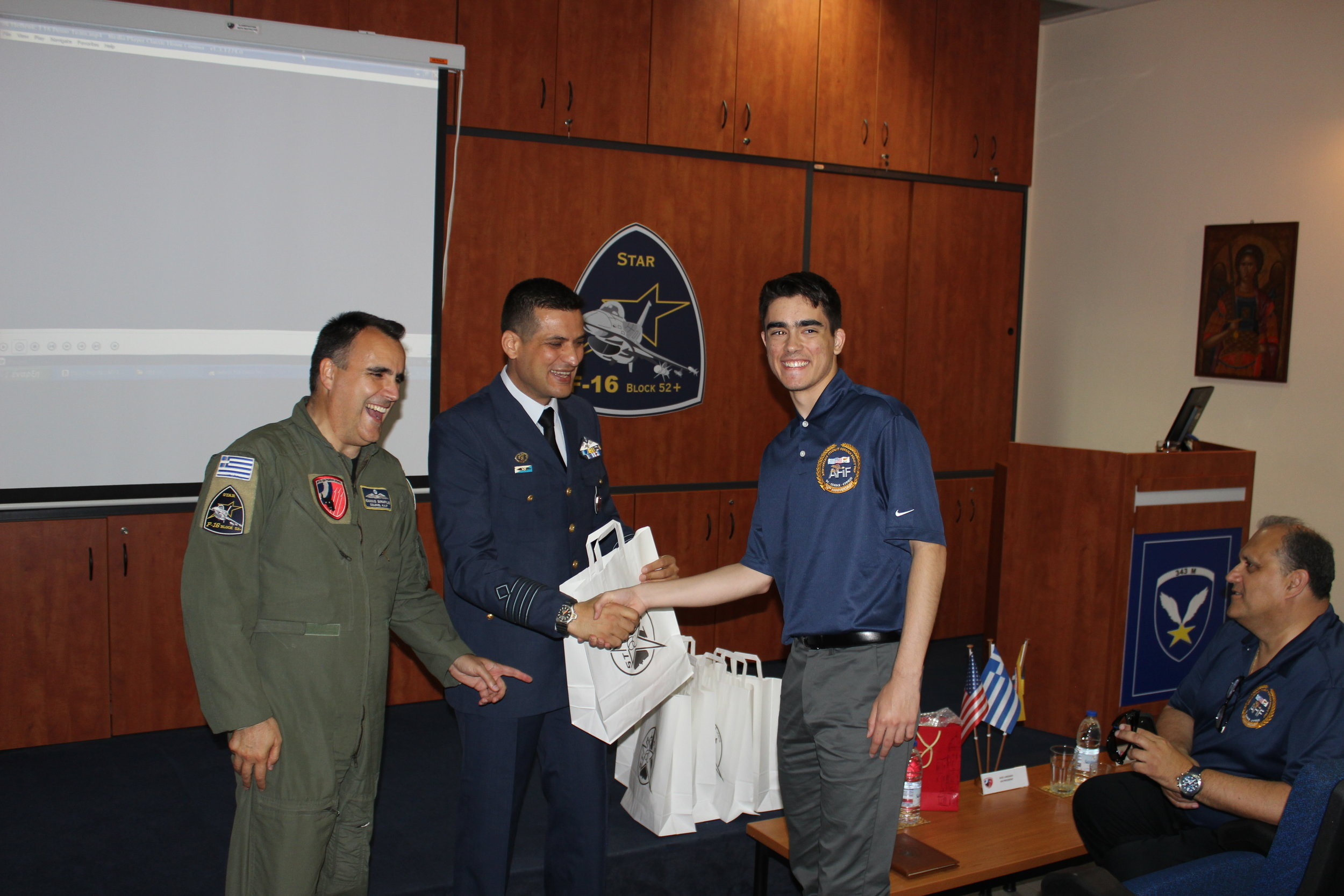 Colonel Ioannis Birbillis (left), commander of the 115th Combat Wing presents the students with gifts.