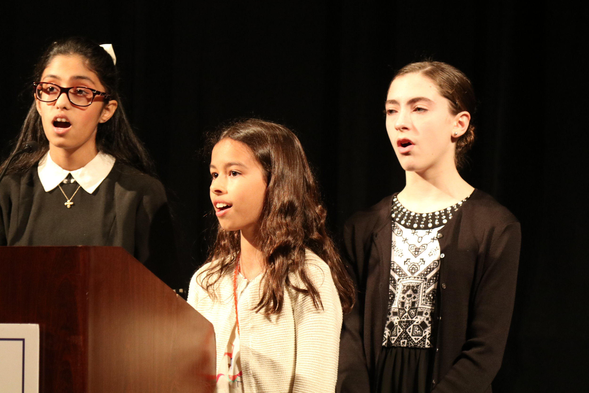 Alexandra Lahiri, Lena Nelson, and Alexandra Dever perform the National Anthems of the United States and Greece.