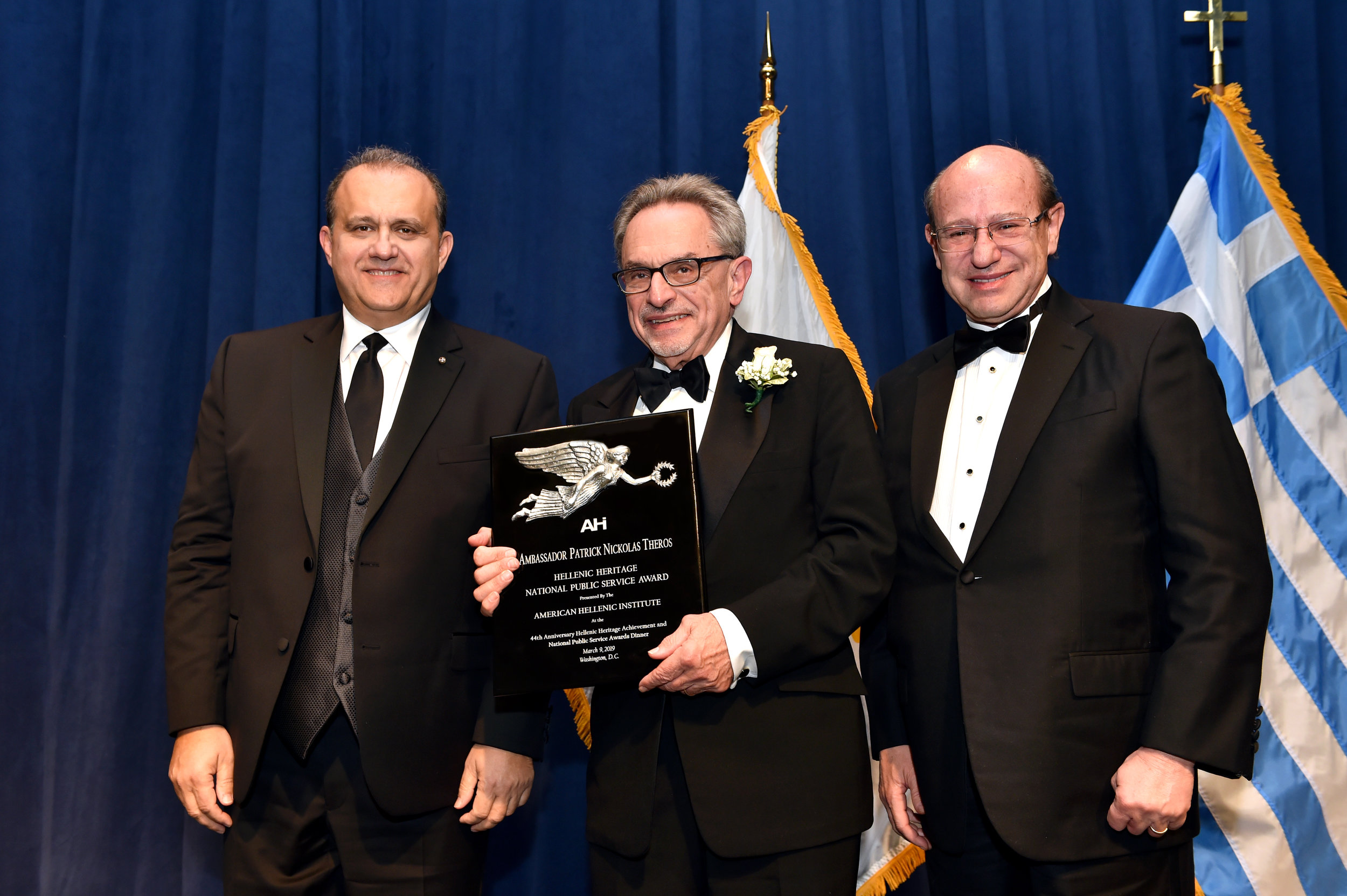 Ambassador Patrick Theros receiving the award from Nick Larigakis and Costas Galanis