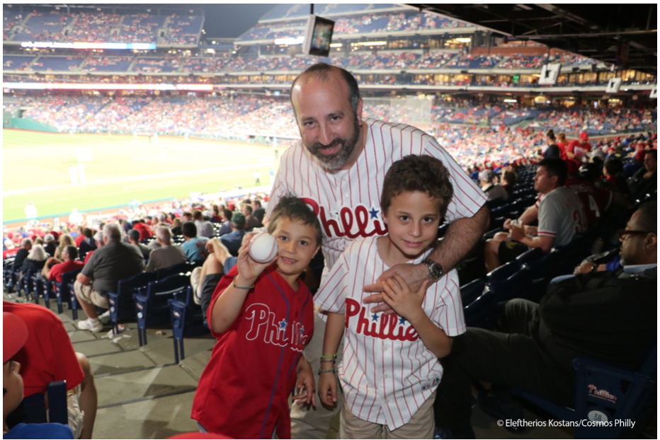 Father enjoying Greek Heritage Night with his sons (courtesy of cosmosphilly.com)