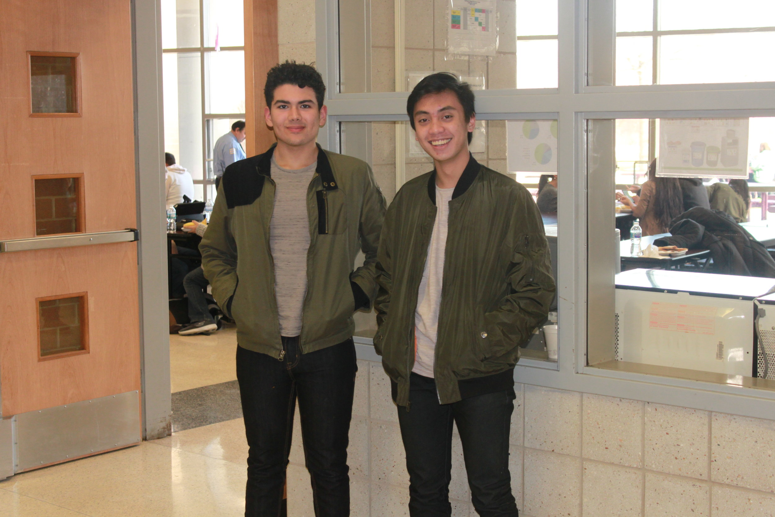Oroin Perez and Resty Fufunan pose with their hands in the dark green jacket pockets.