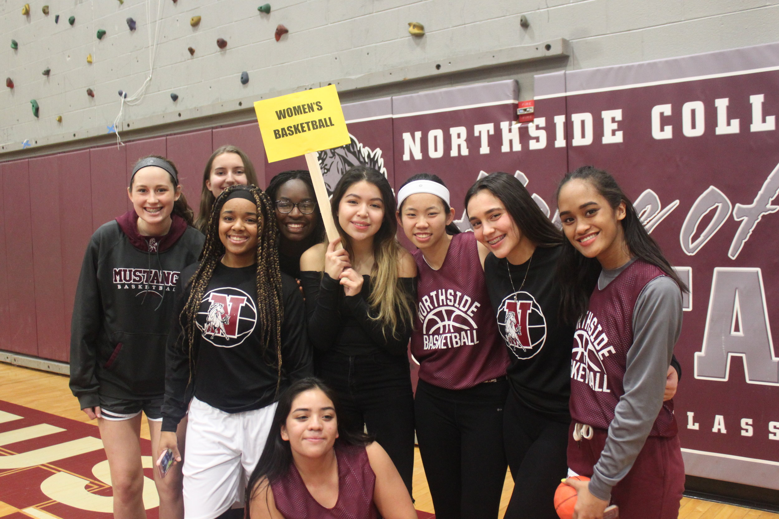 The basketball team smiles in spirit of their homecoming game after school.