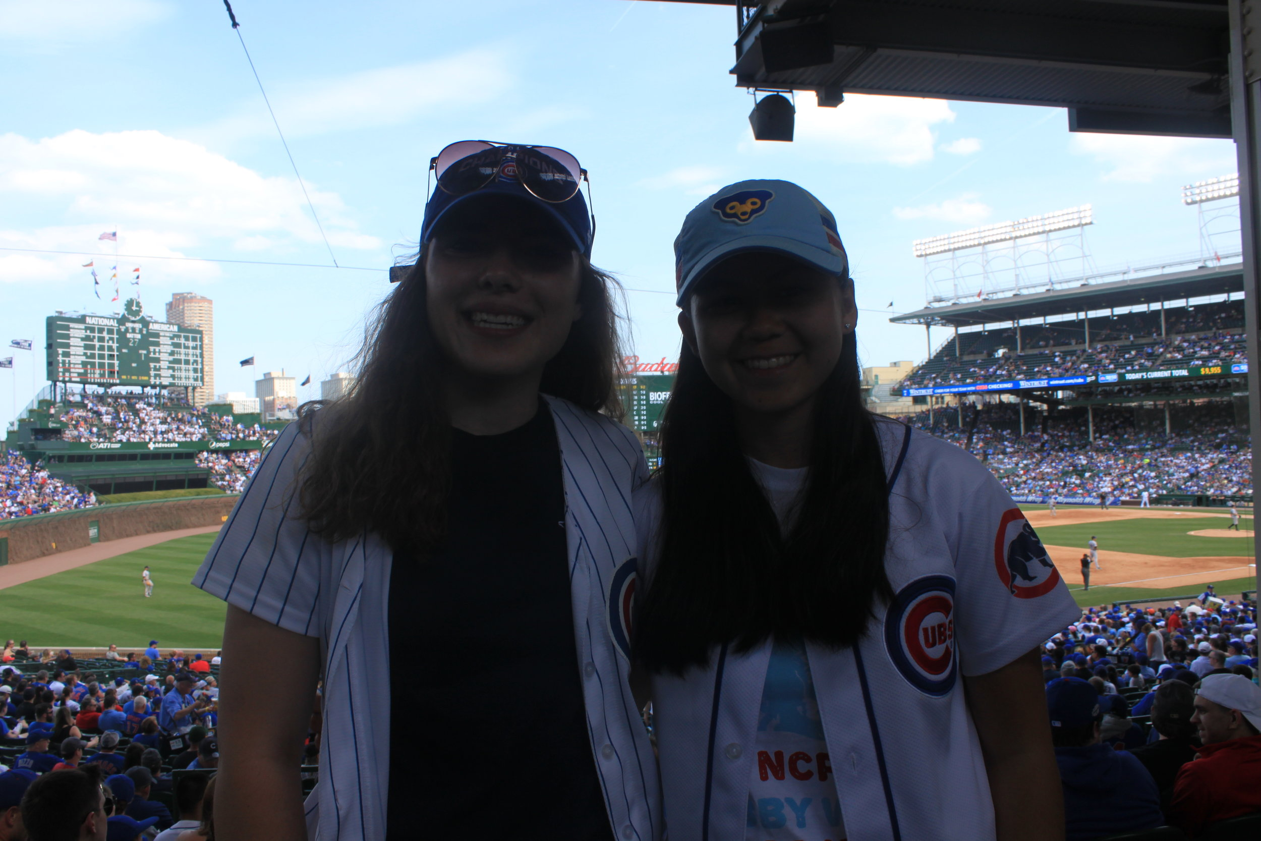 Madeleine Schoeff and Audrey McManus smile as they cheer on the Cubs.