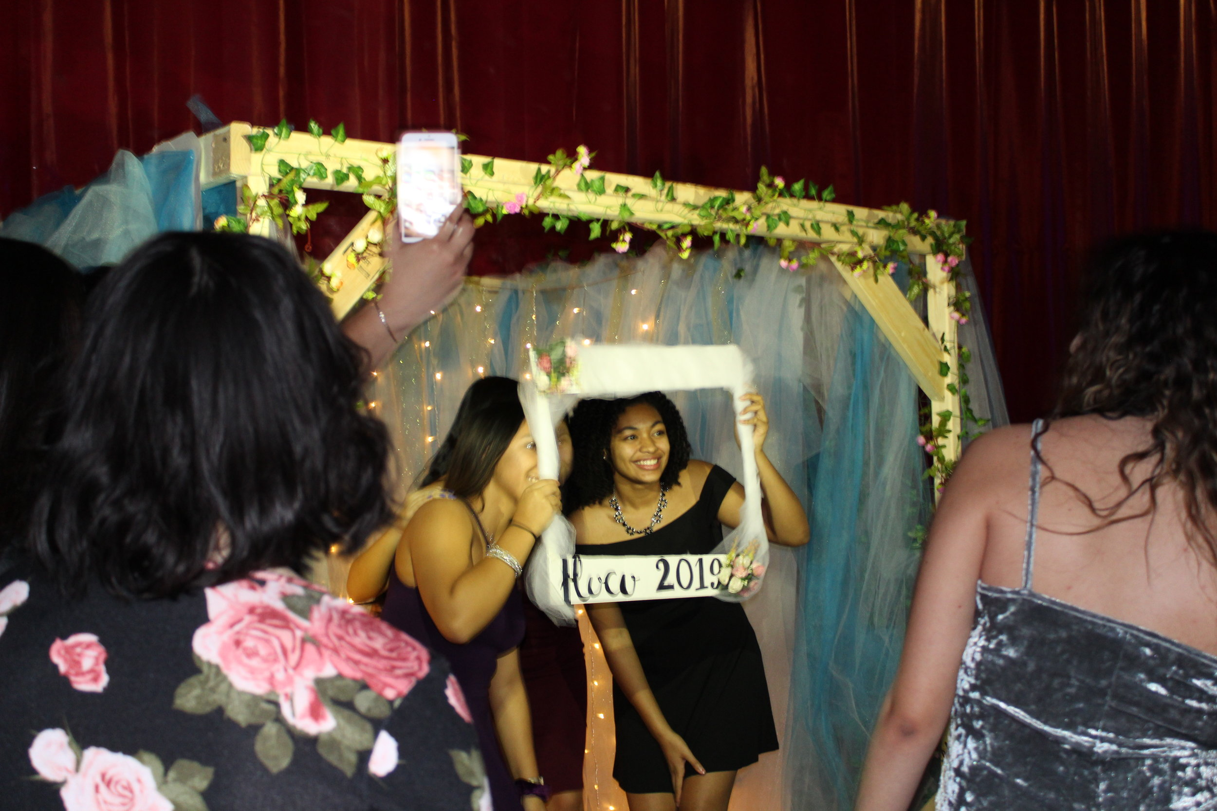 A group of students hold up the frame in the photo booth