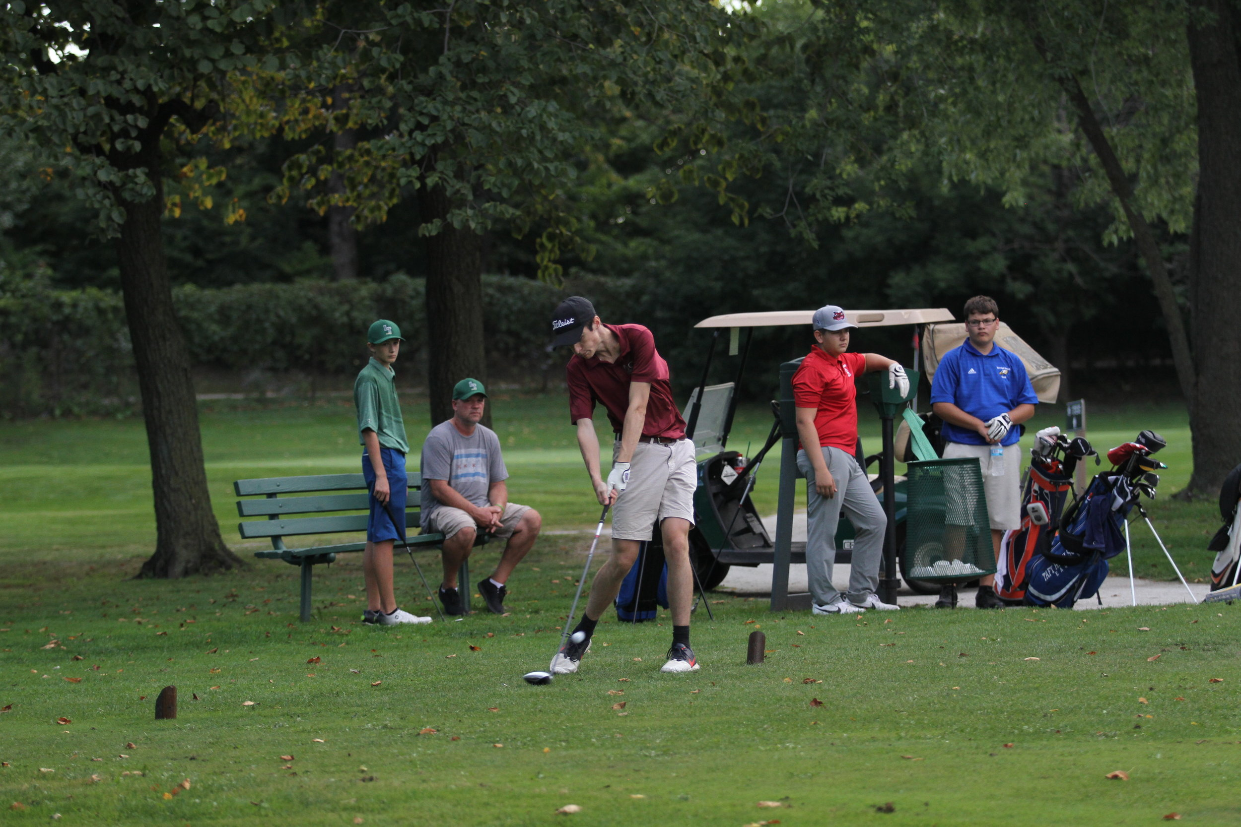 Danny flexes his neck muscles while playing some very intimidating opponents in a golf match.