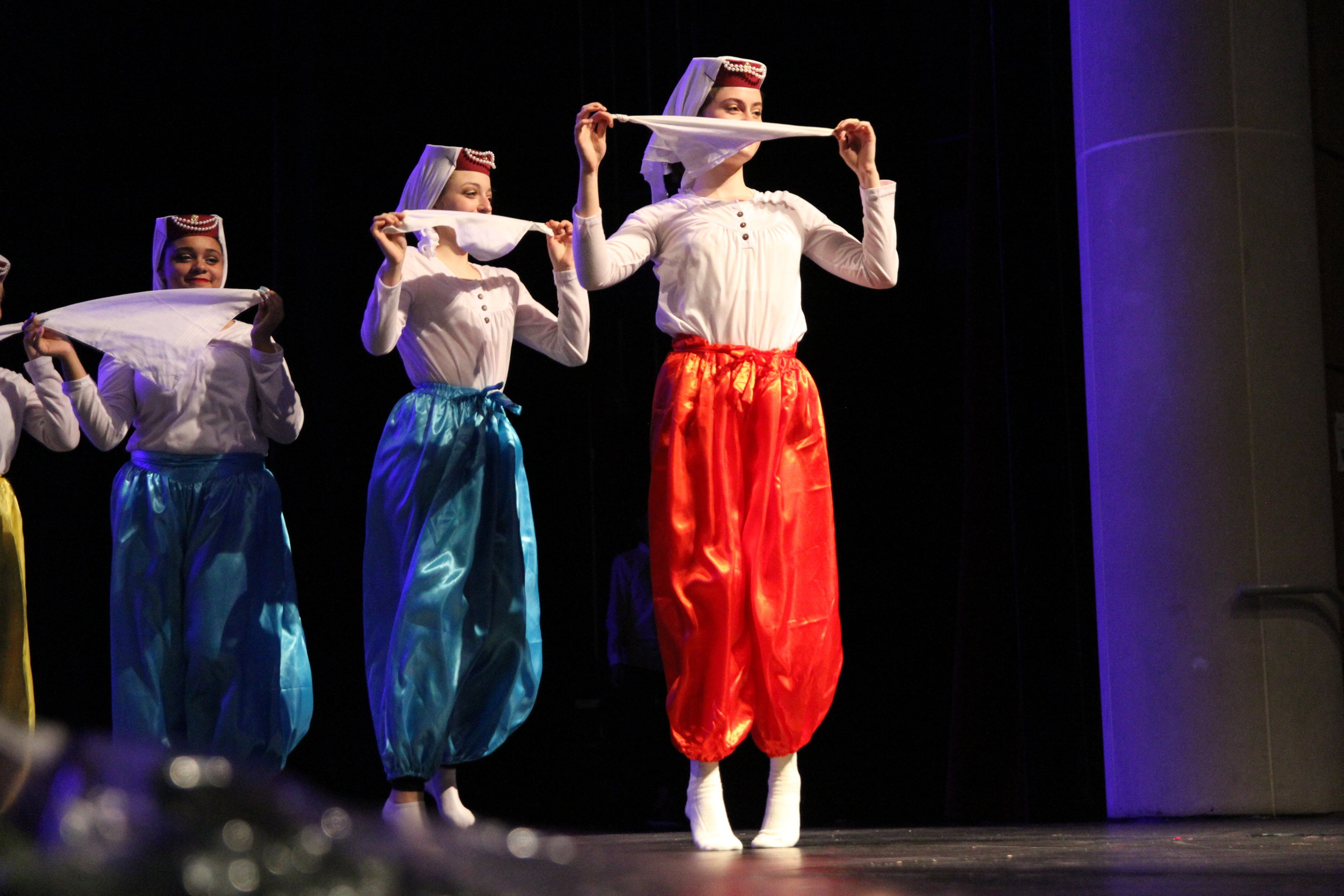 Edina Hadzic, Adv. 905, and her fellow dancers float around the stage in their brightly colored Harem pants as they hide their faces behind handkerchiefs