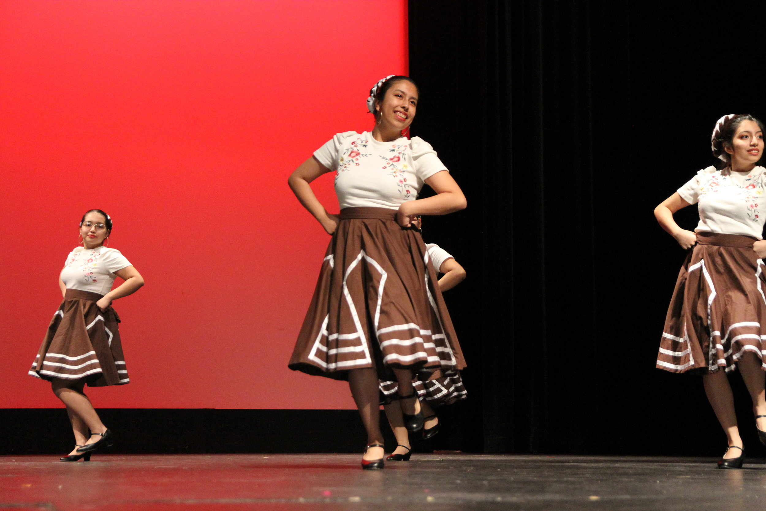 Brianna Gonzalez, Adv. 900, smiles at the crowd as she begins to turn in her classic Mexican attire