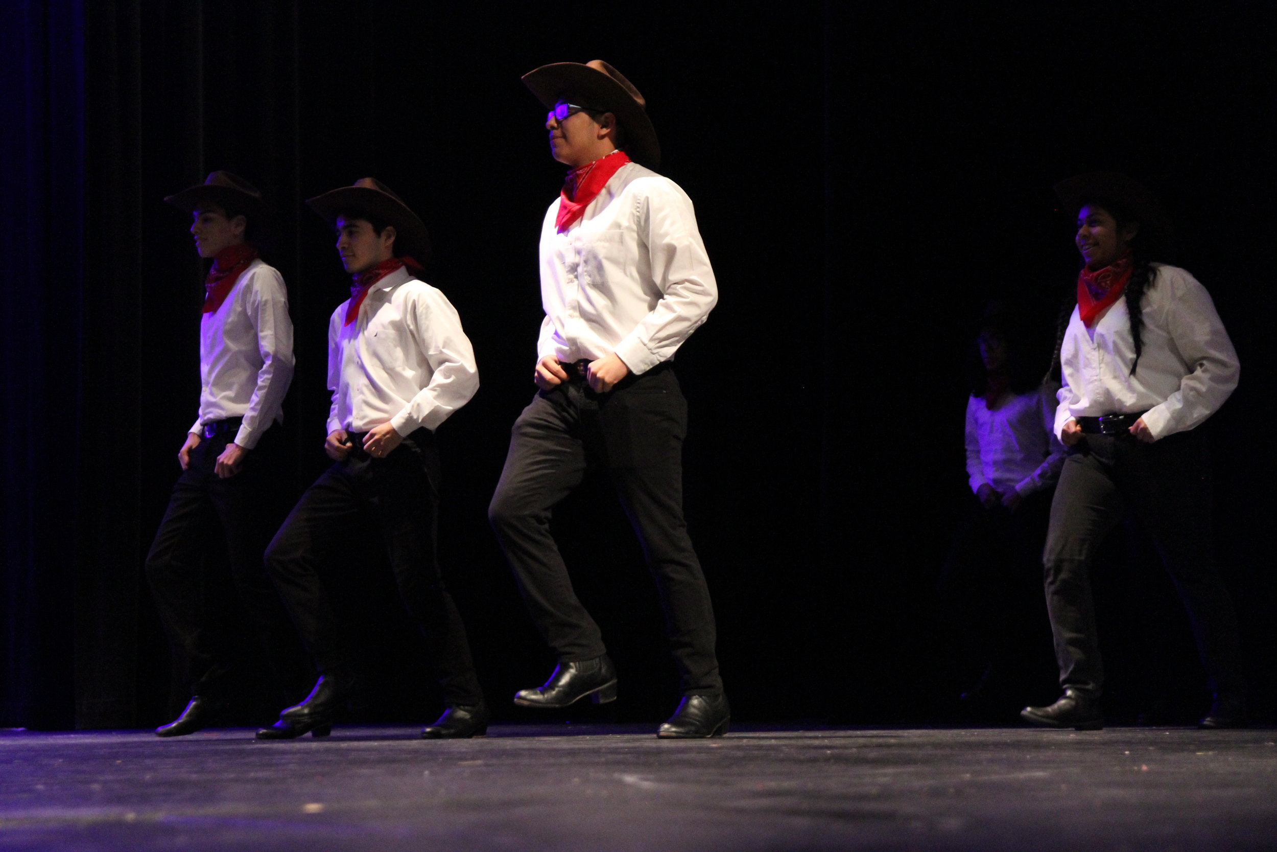 The men of Folklore Rico stomp out onto the stage in their cowboy hats and with red handkerchiefs around their neck