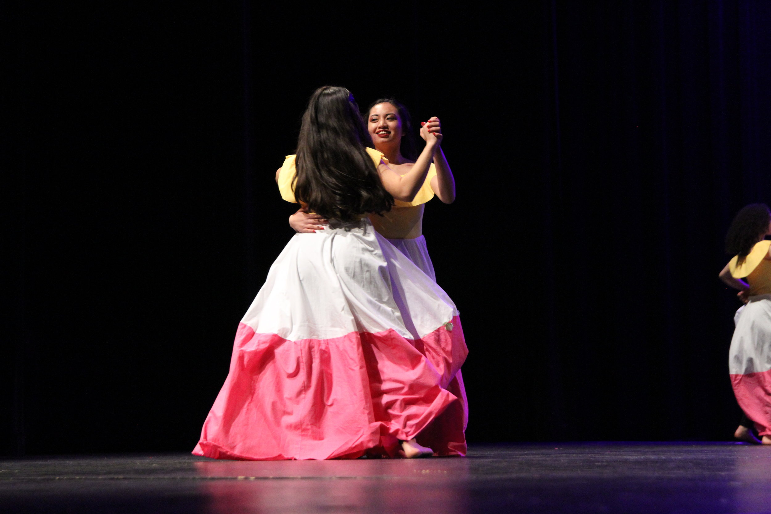 Two women of Jamaican Dance dance together as their flowing two-tone skirts follow behind them
