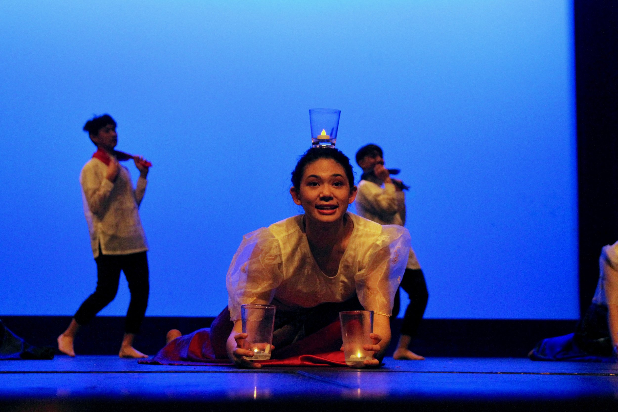 Olivia Tavas, and her fellow dancers in the first part of the dance of Isang Hakbang, carefully balance candles on their heads as they waltz around stage