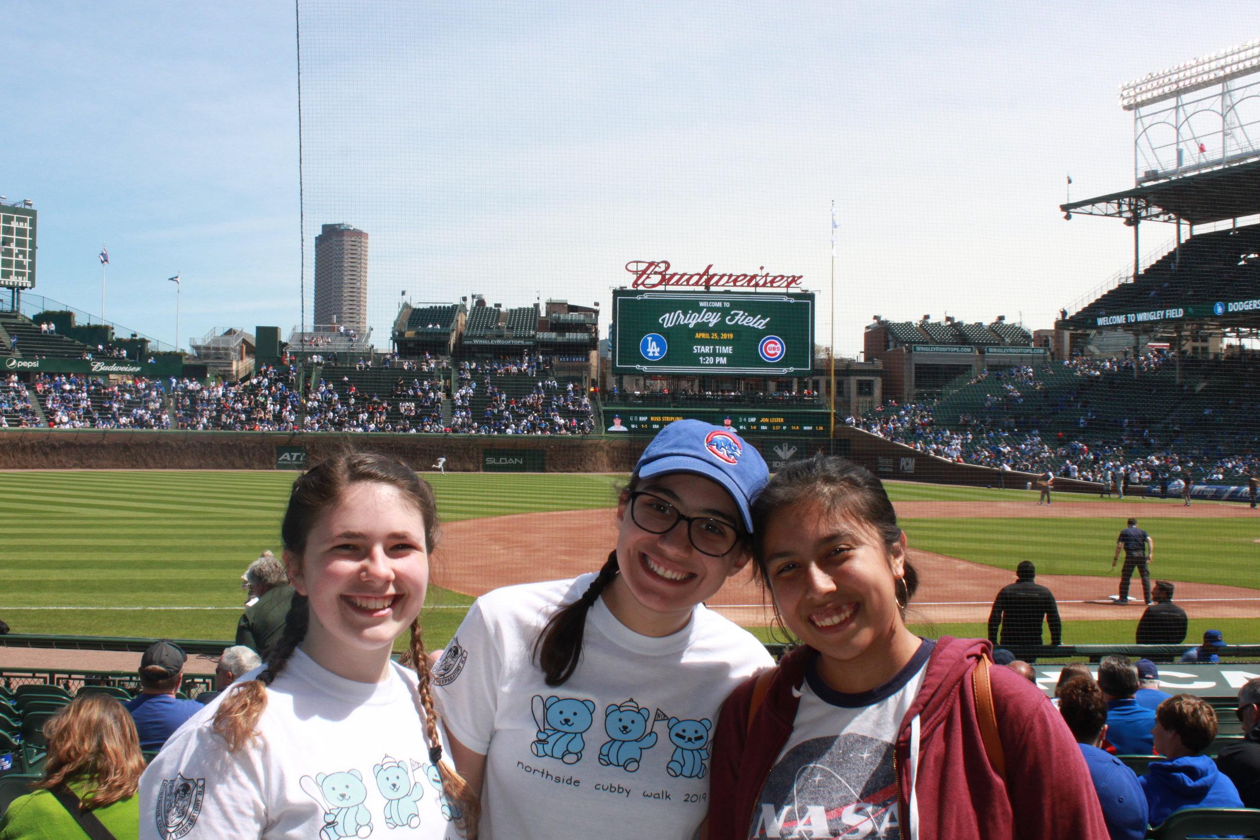 Savannah Graziano, Adv. 903, Audrey Ruhana, Adv. 903, and Brianna Gonzalez, Adv. 900, pose in front of the scoreboard.