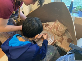 Students from Mrs. Minyo's Ceramics II course helped children throw pots on the pottery wheel.