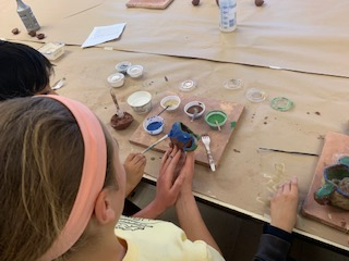 Children were taught how to make pinched pots into varying sized pots and individualize them with paint and texture