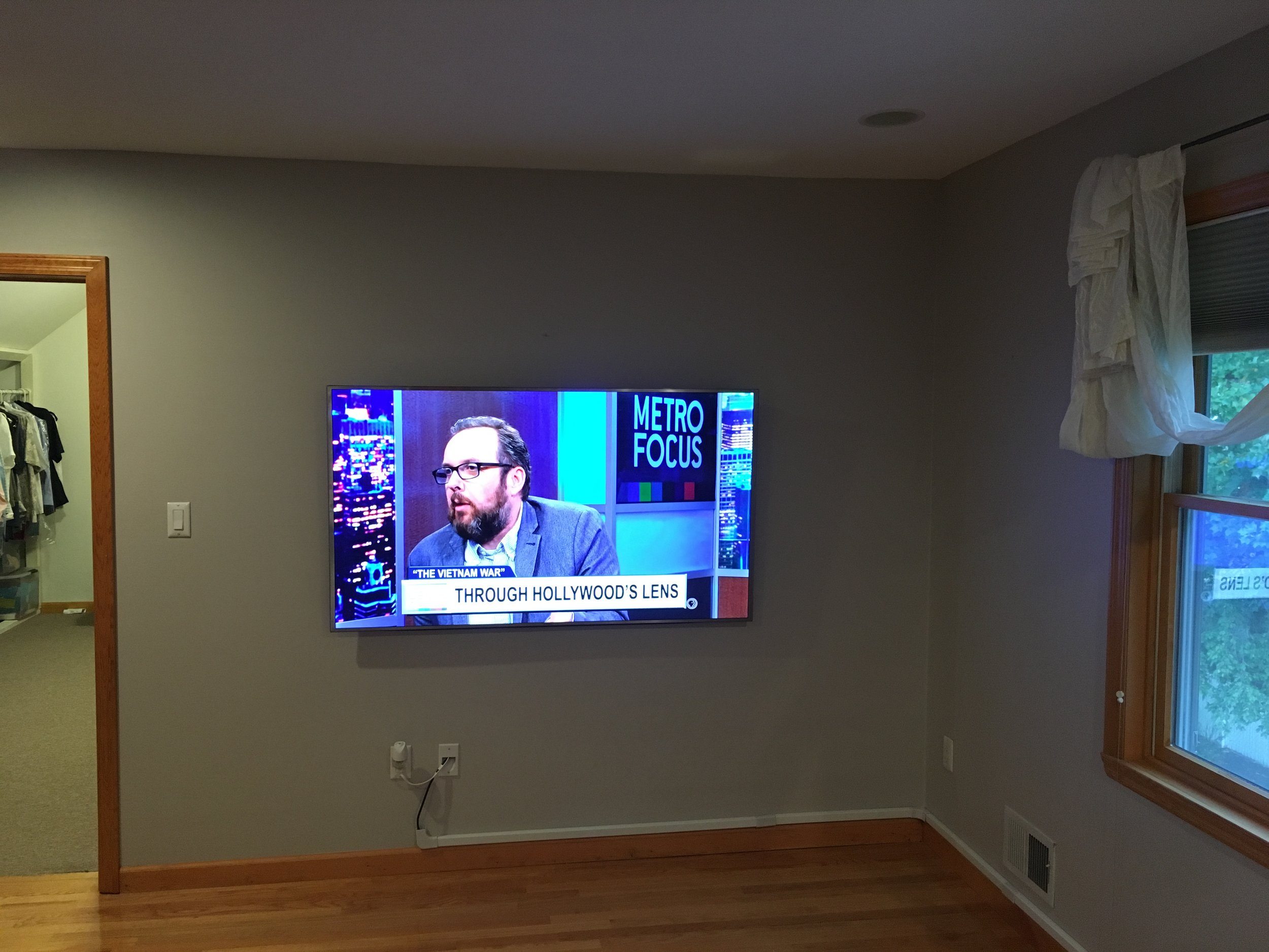 "65"" TV Mounted in bedroom with all wires hidden, and cable box mounted behind TV."