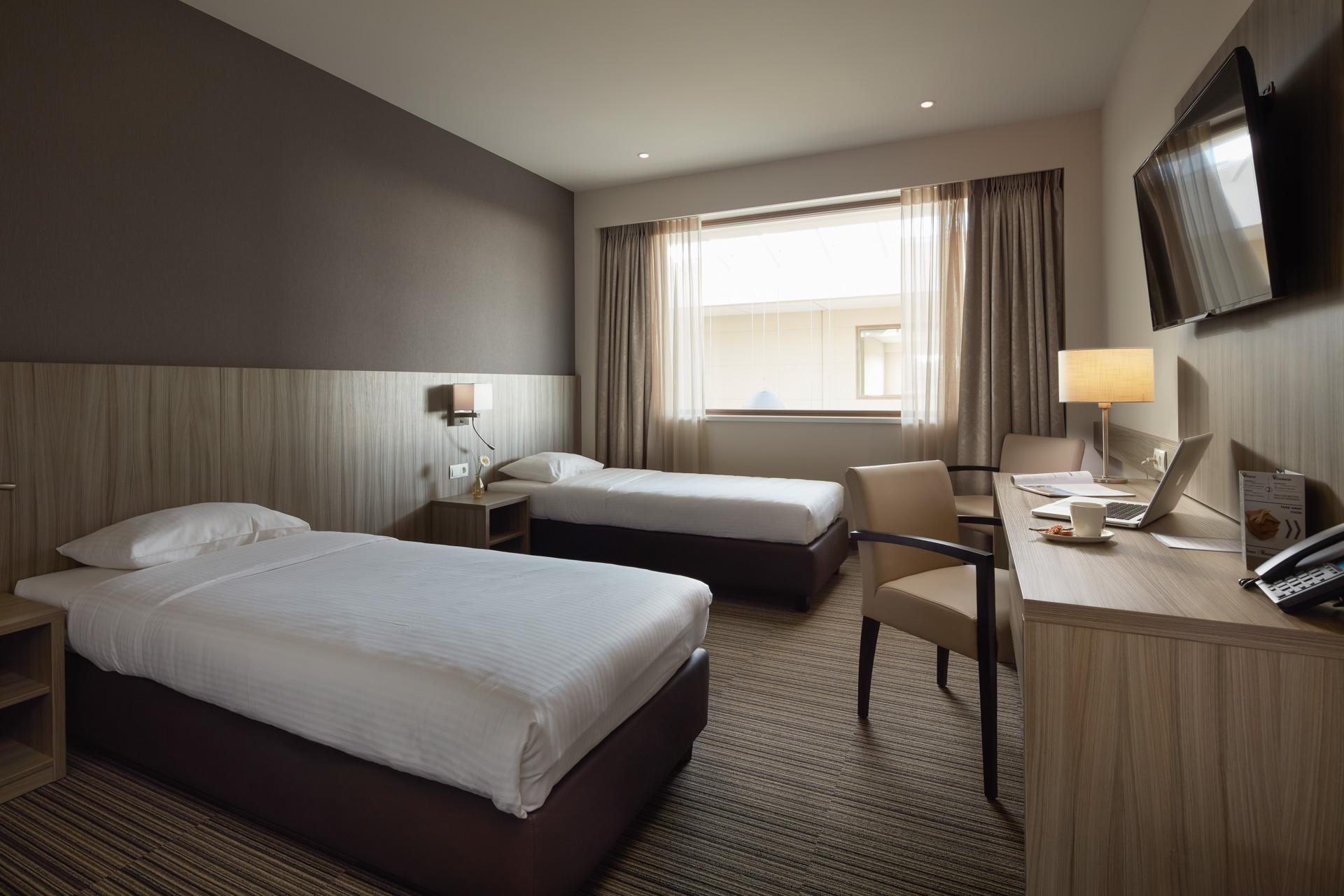 Beringen | Interieur hotelkamer met twee enkel bedden en laptop op bureau