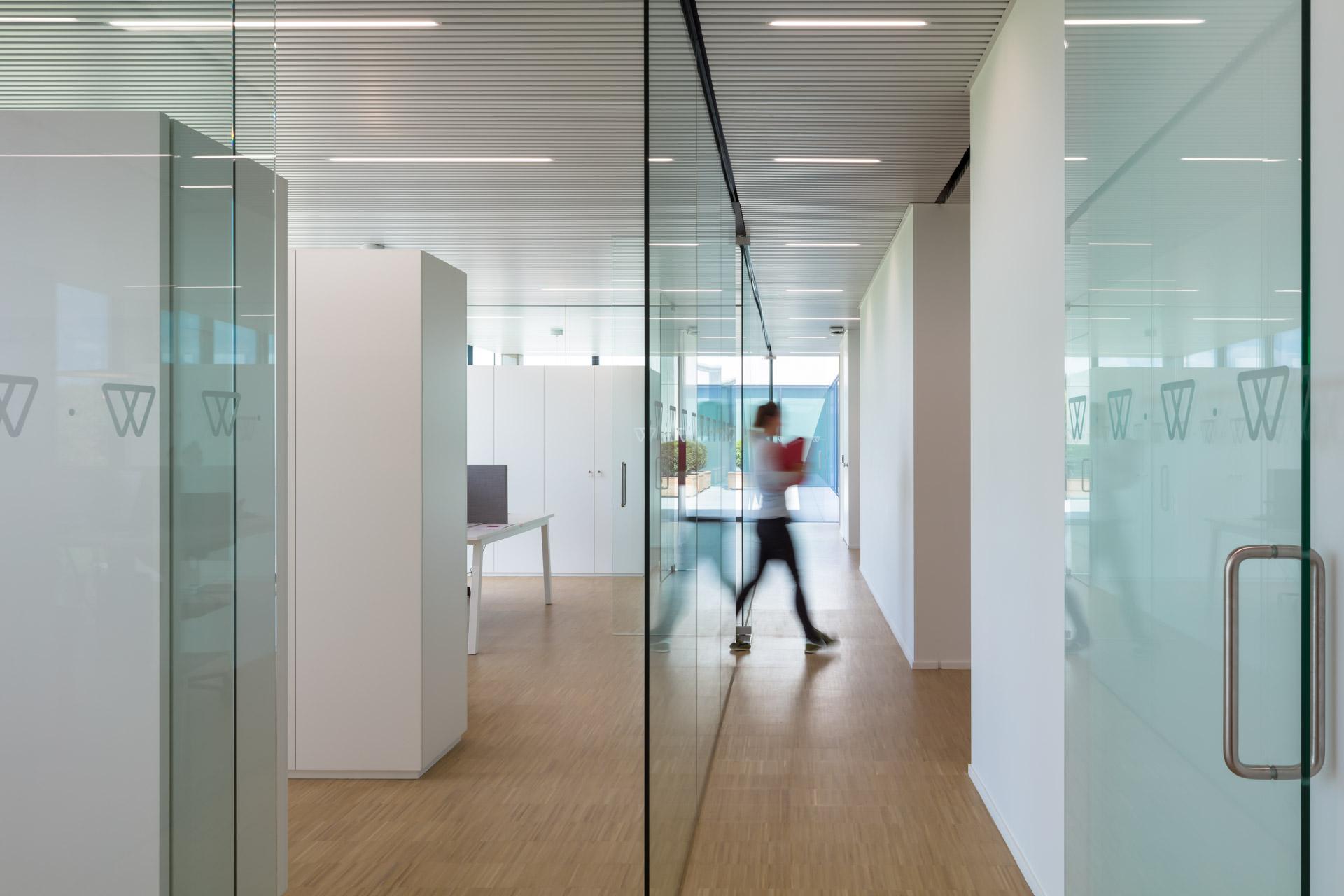 Geel | interieur van kantoor - vrouw loopt door gang