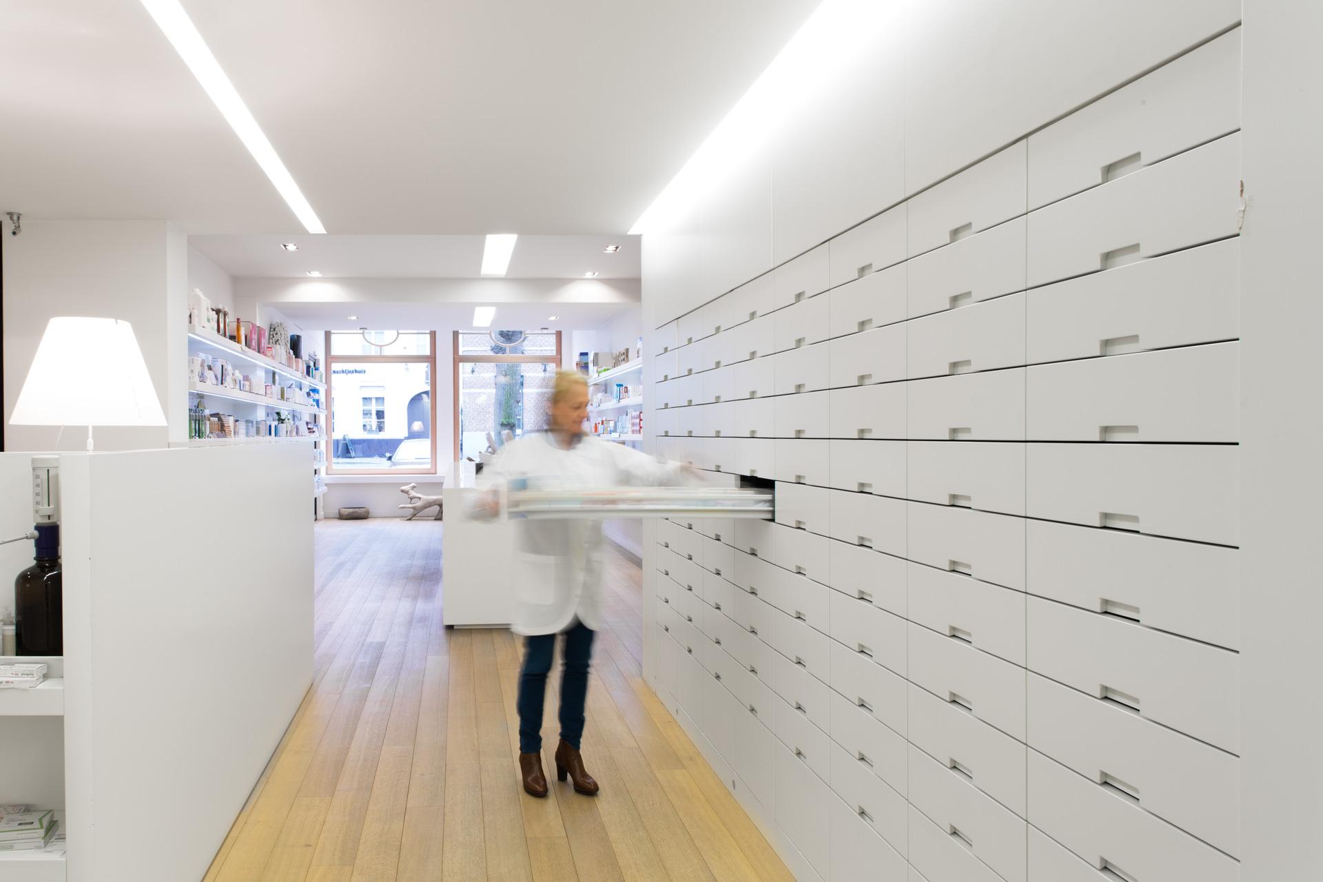 Hoogstraten | Interieur van apotheek, vrouw trekt schuif open