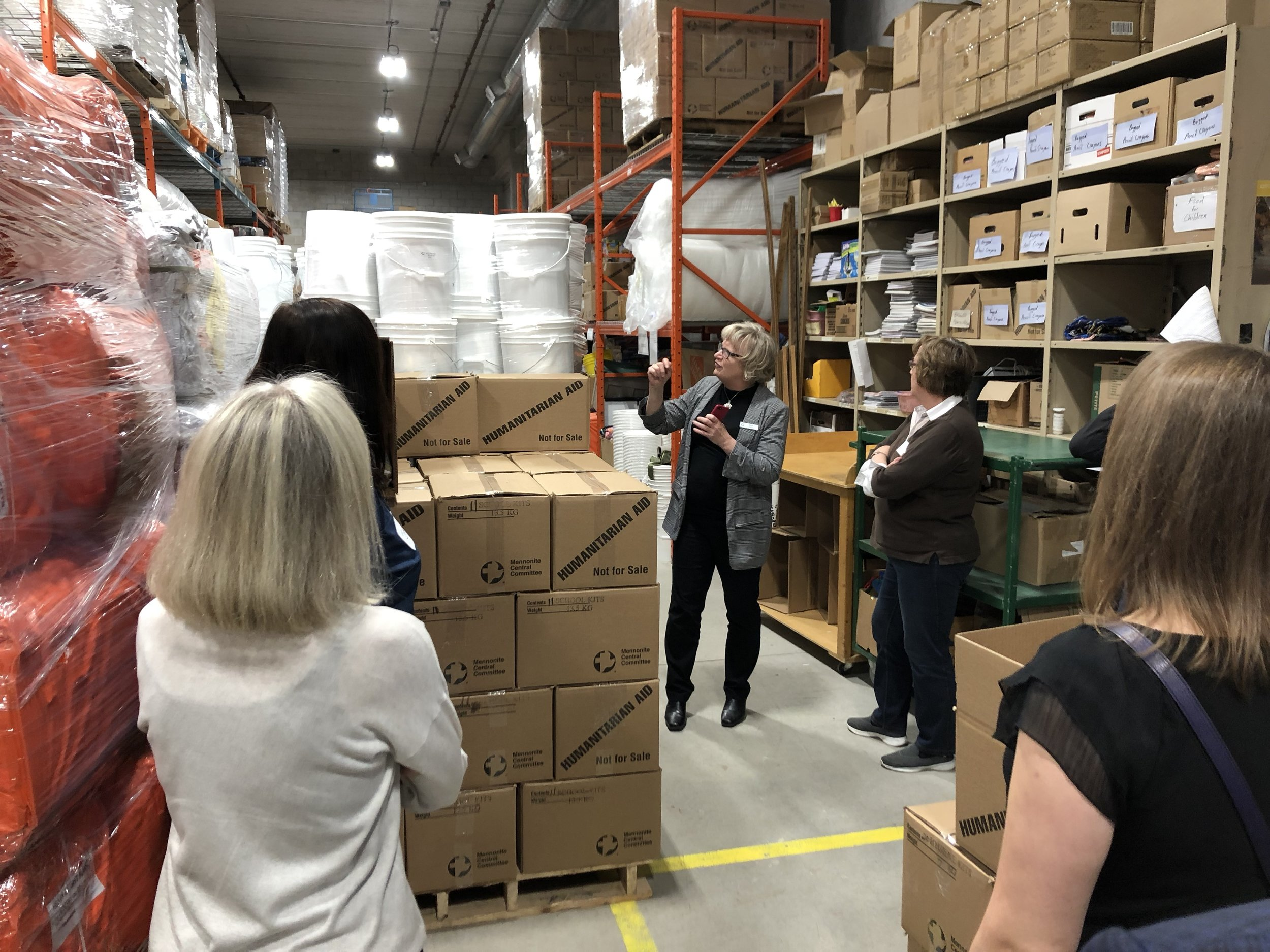 Associate Executive Director Kim Lester showing the group a shipment of relief kits, set to ship overseas just days after our site visit.