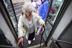 Elderly women with cane getting on a bus