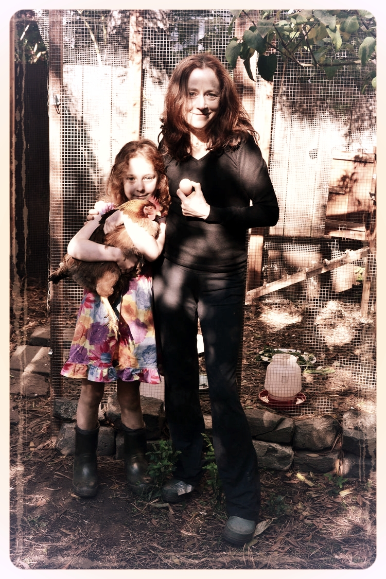 Leslie Crawford, author of Sprig the Rescue Pig, and her daughter Molly at home in front of their chicken coop.