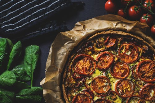 Top whole wheat pizza dough with roasted vegetables for a healthier quick meal.