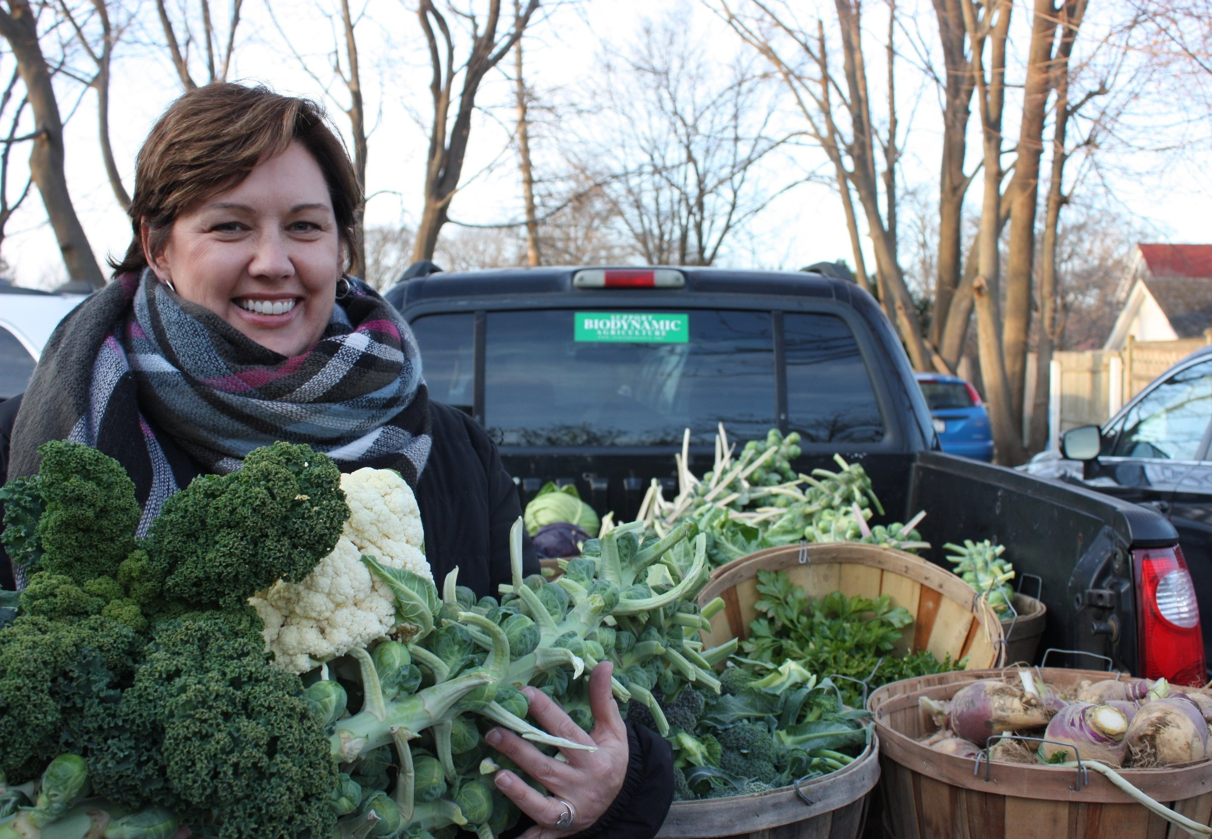 Cathy Demeroto, Executive Director of CAST, with an armful of donated vegetables.