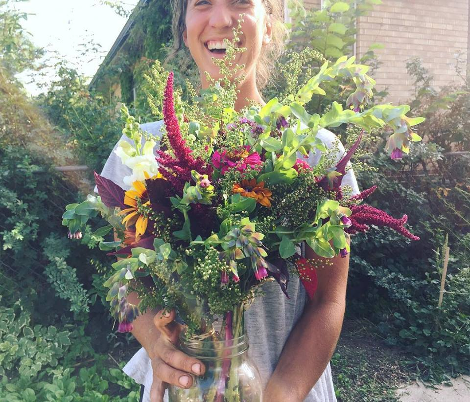The Veg Yard founder Maddy Torraca Jones holds a bouquet of flowers from the farm's flower share.  Photo source