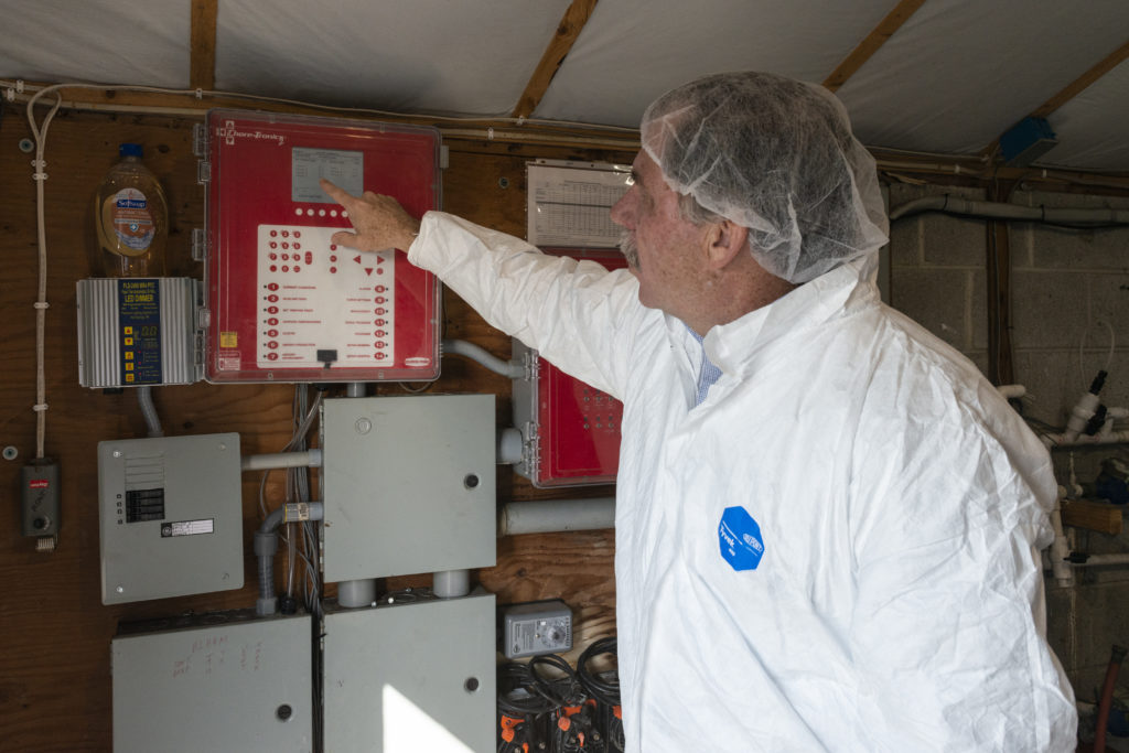 Mike Levengood points out the central control system that maintains the temperature and humidity inside of each chicken barn, depending on the stage of growth of the chickens inside.