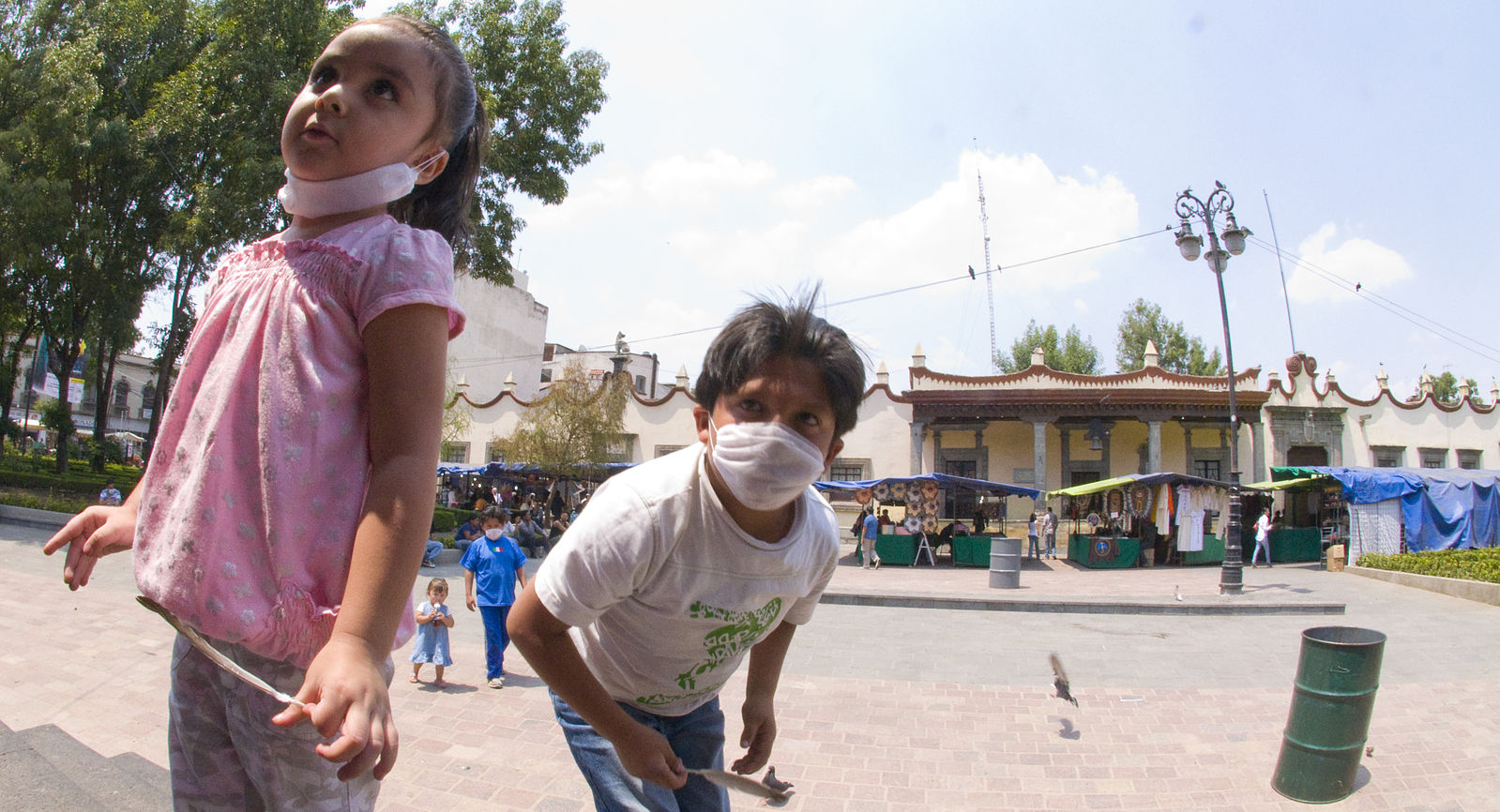 Children in Mexico wear masks during the 2009 swine flu outbreak. New flu pandemics are just one of the many public health crises linked to factory farming.  Image source
