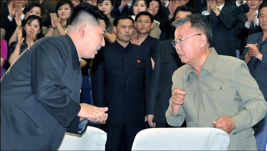 KJU uneasily confers with his father, Kim Jong Il. The man in the middle is KJU's uncle.